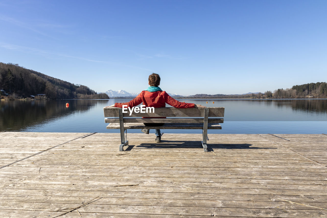 Rear view of woman sitting on bench over lake against sky