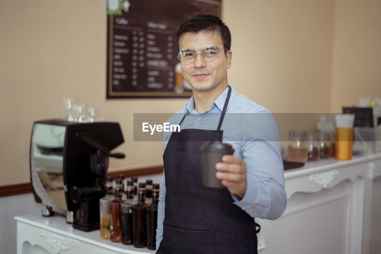 PORTRAIT OF A SMILING YOUNG MAN WITH DRINK IN RESTAURANT