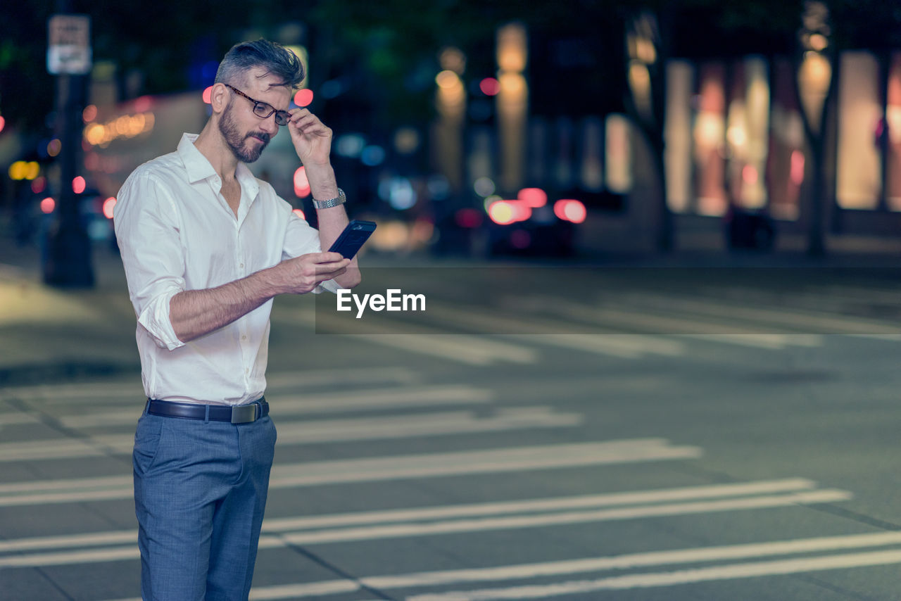 Businessman Using Phone While Standing On Street At Night