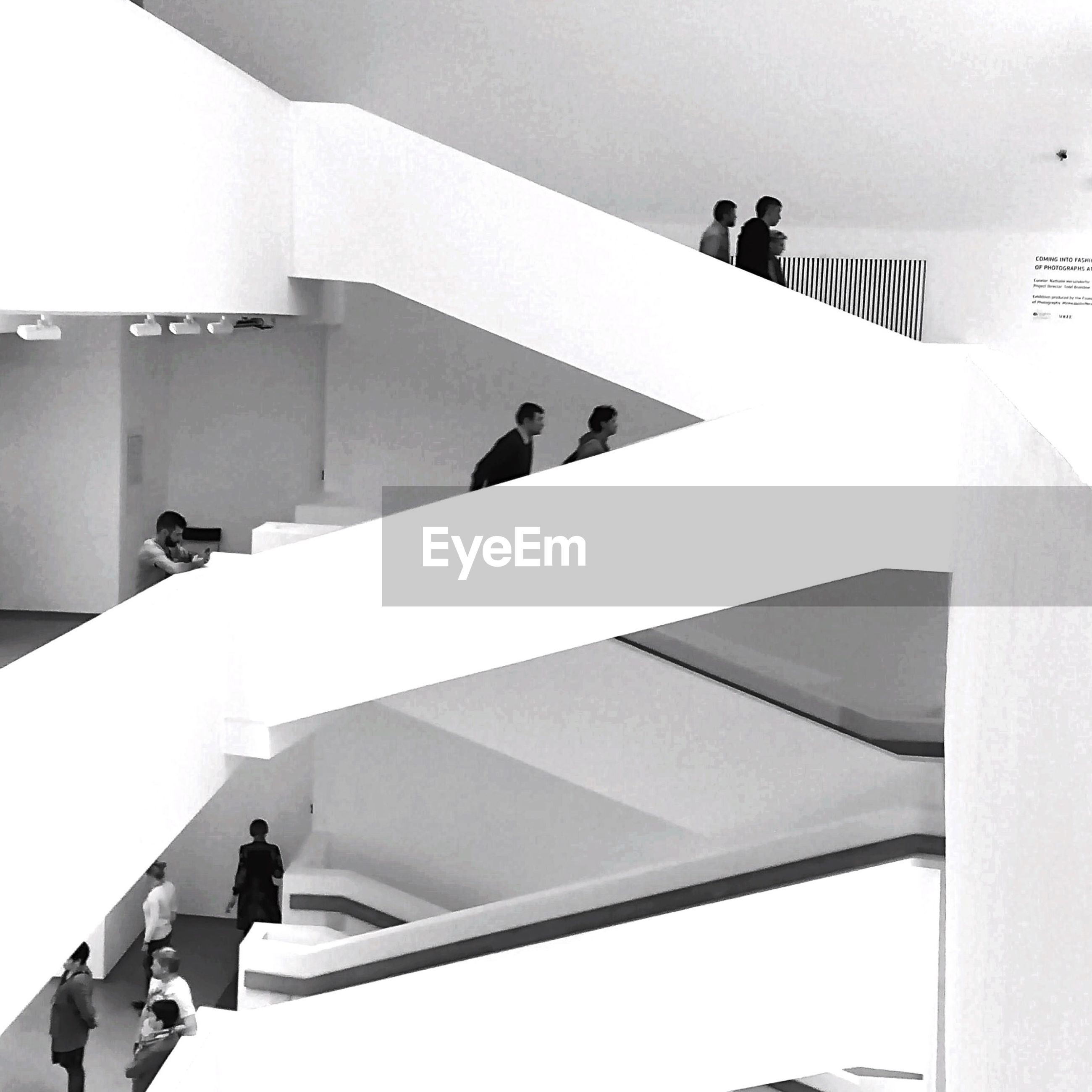 low angle view, built structure, architecture, men, lifestyles, white color, steps, railing, building exterior, staircase, walking, day, steps and staircases, leisure activity, indoors, full length, unrecognizable person