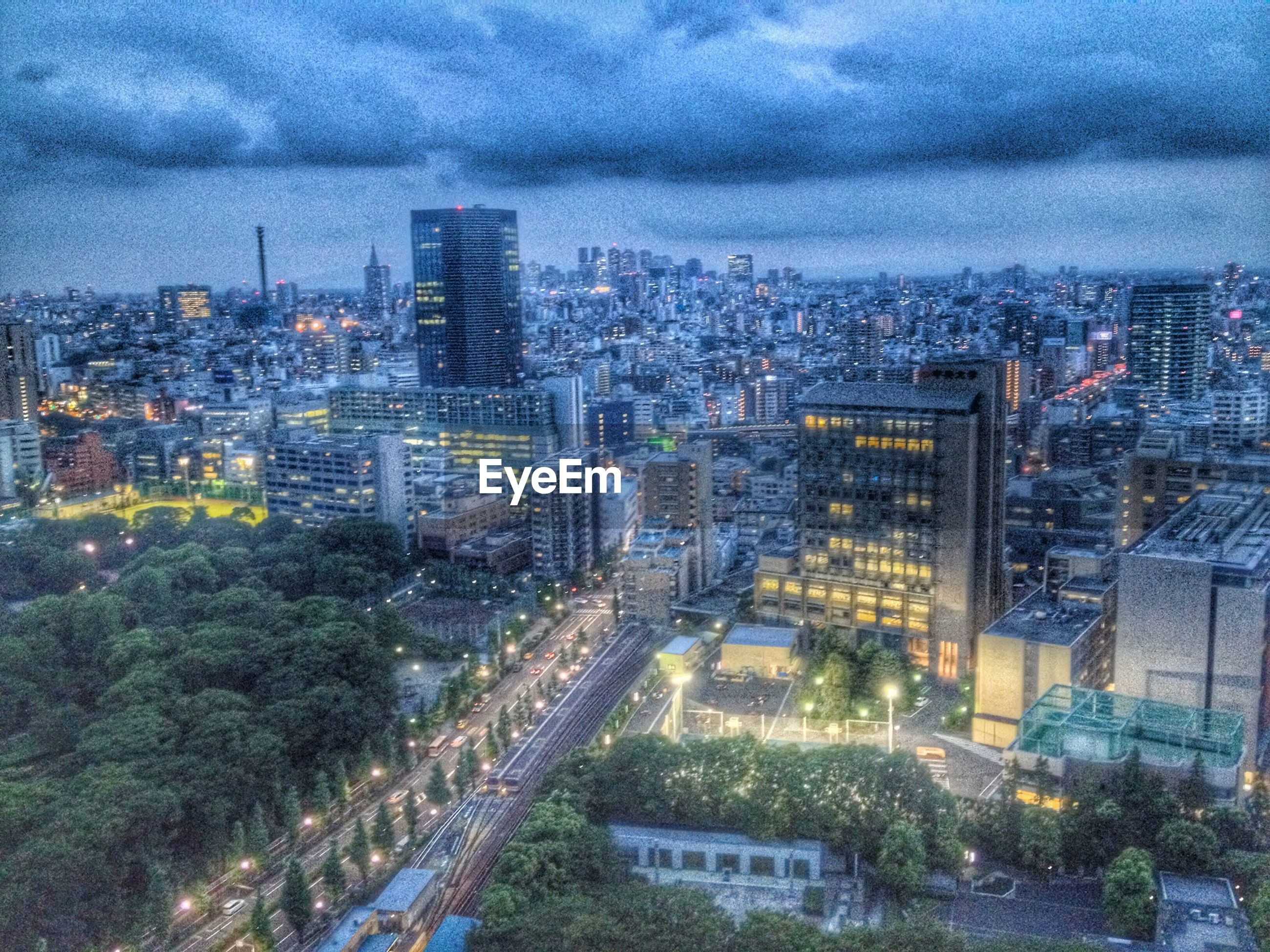 building exterior, city, architecture, built structure, cityscape, sky, cloud - sky, high angle view, skyscraper, illuminated, road, city life, residential building, residential district, modern, office building, cloudy, crowded, street, transportation