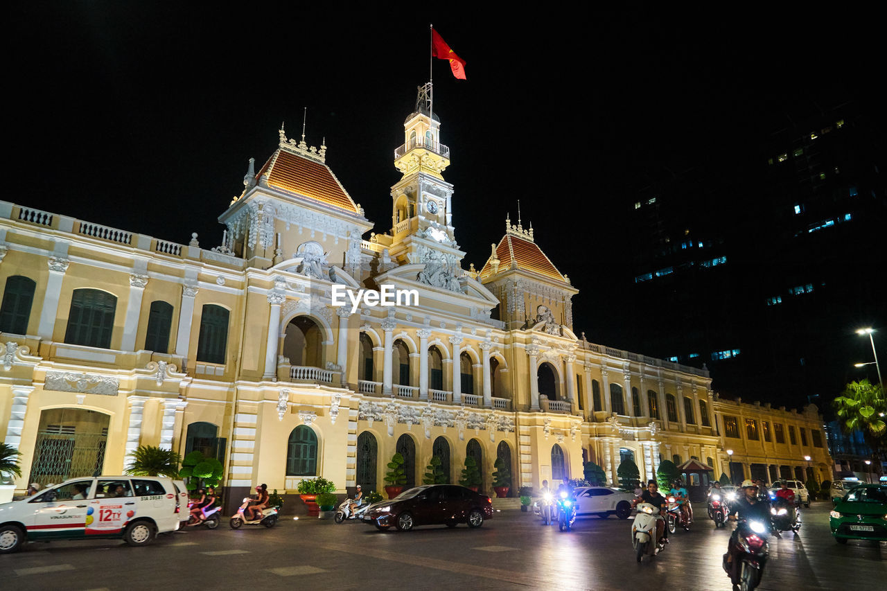night, architecture, built structure, building exterior, illuminated, flag, real people, large group of people, outdoors, travel destinations, city, sky, people