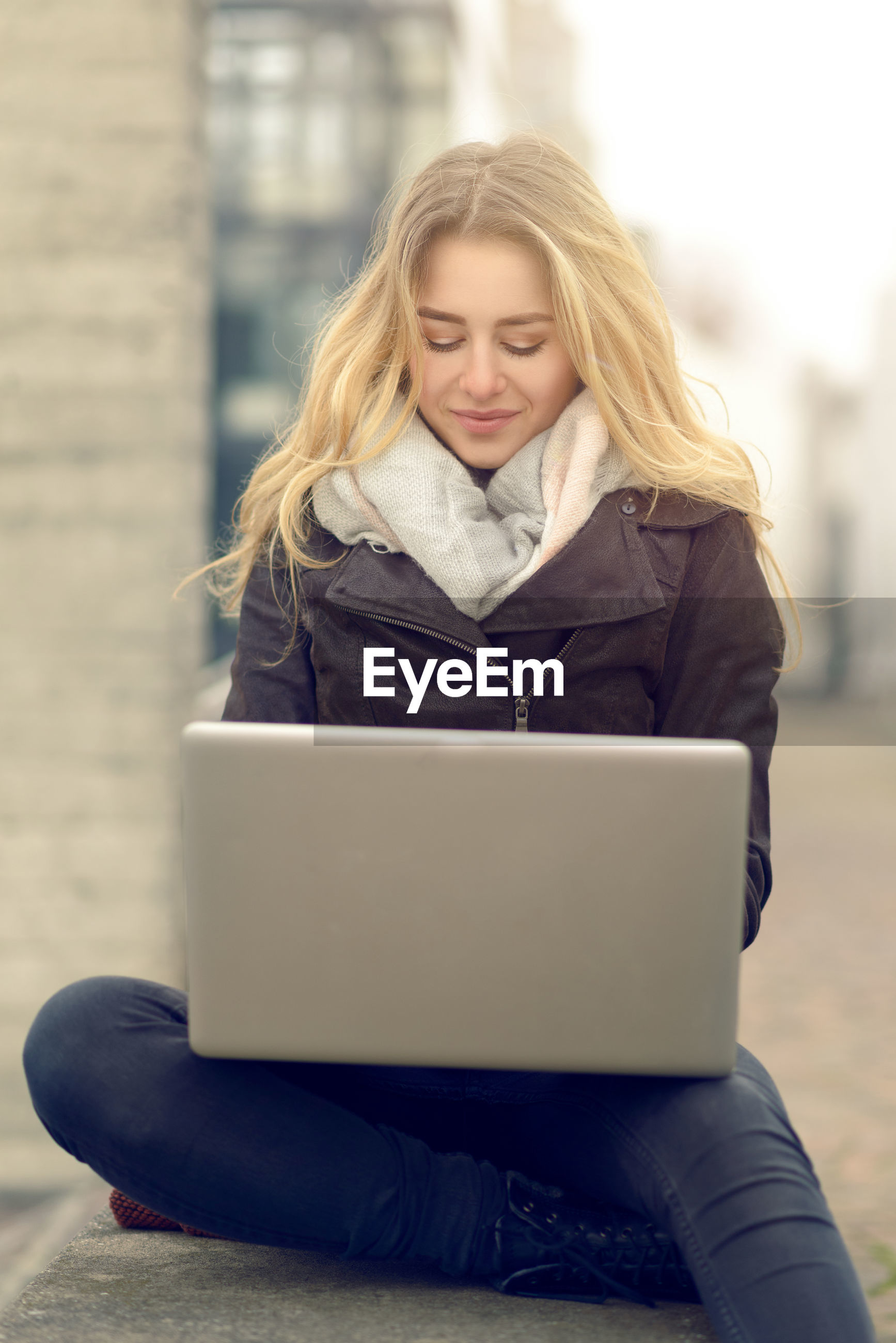 Young woman with blond hair using laptop outdoors