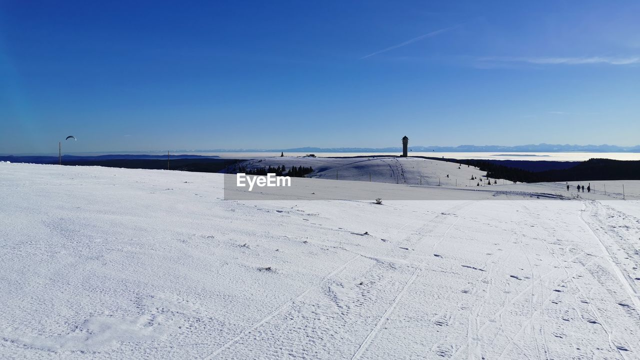 Scenic view of snow covered landscape against blue sky