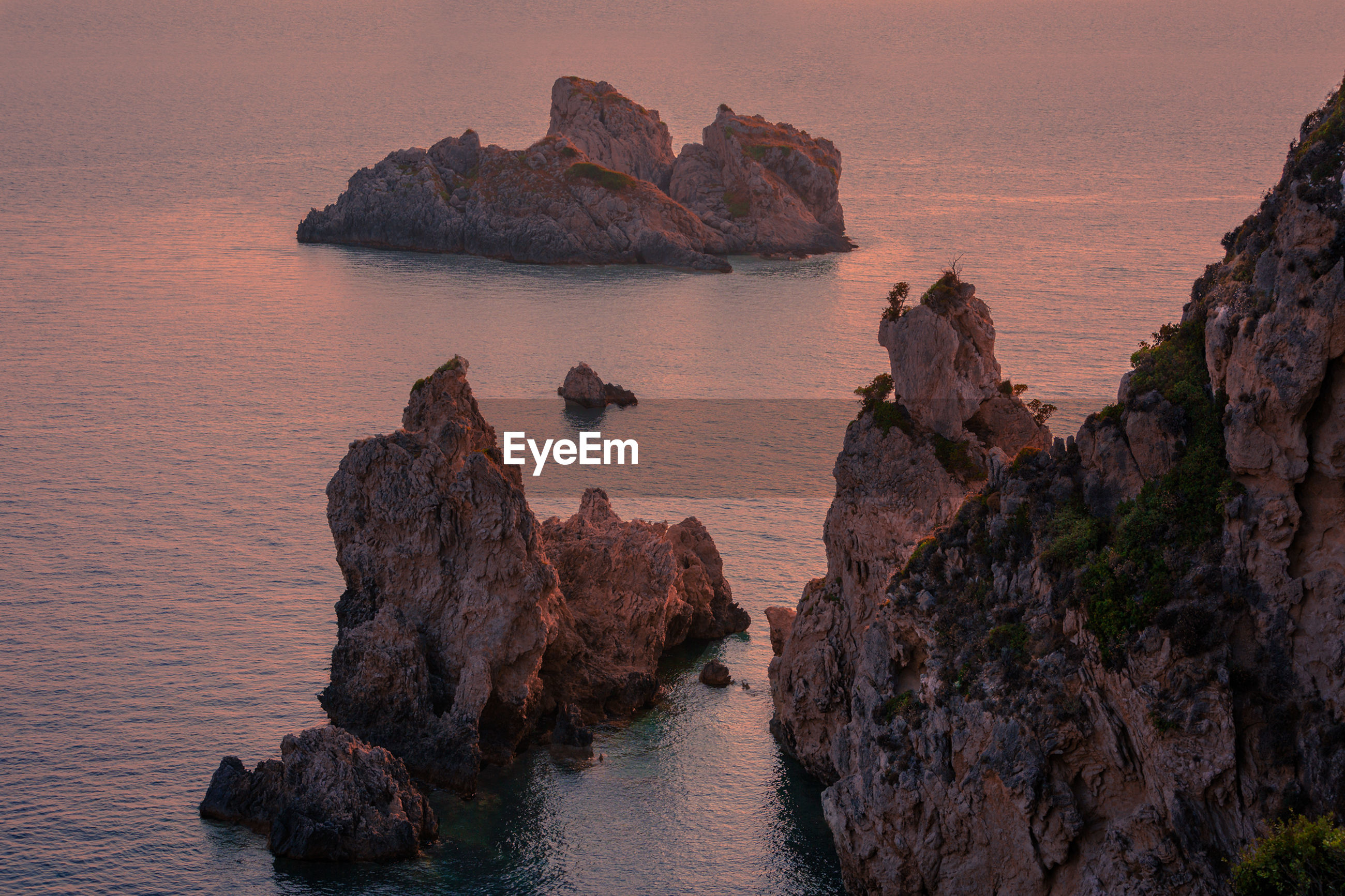 High angle view of rock formations and sea during sunset