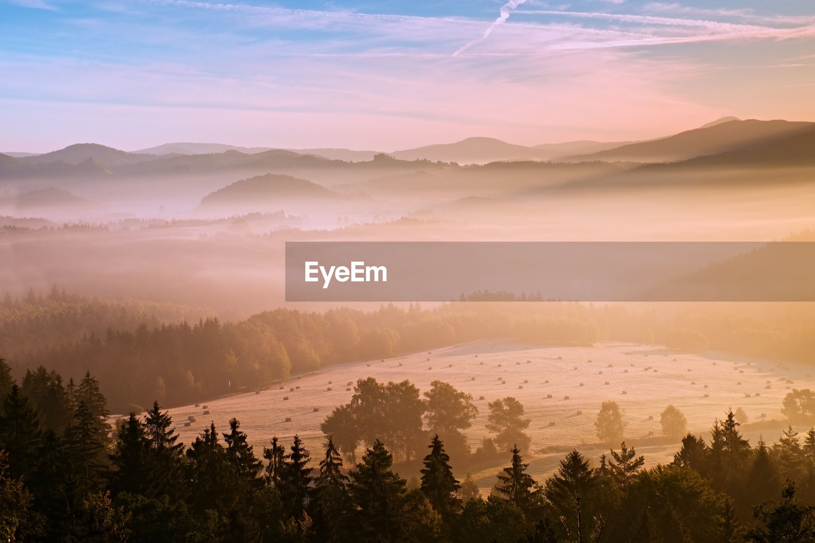Pink daybreak in hilly landcape. autumn misty morning in beautiful hills. peaks of hills in mist