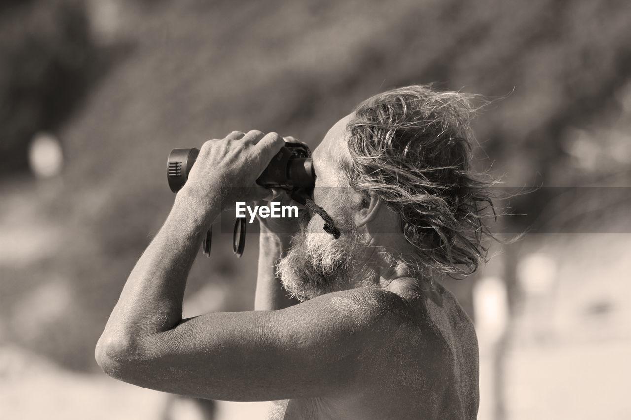 Side View Of Senior Man Looking Through Binoculars
