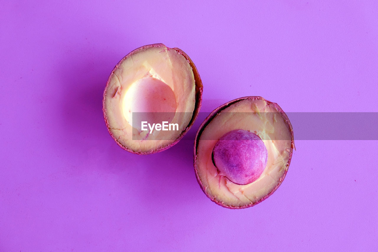 freshness, food and drink, healthy eating, pink color, indoors, fruit, food, still life, wellbeing, studio shot, close-up, cross section, colored background, halved, pink background, no people, purple, high angle view, purple background, copy space, ripe, passion fruit, temptation