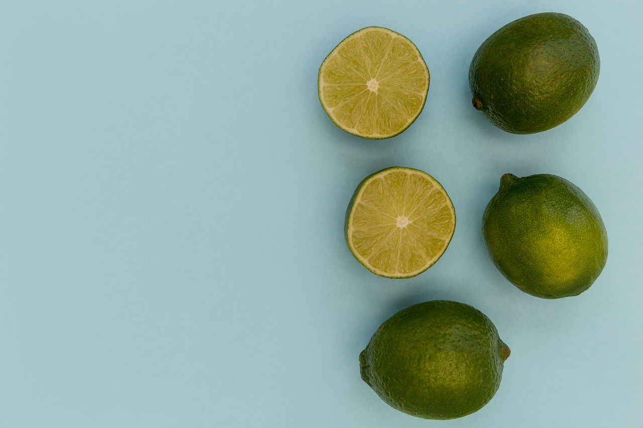 Close-up of limes over blue background