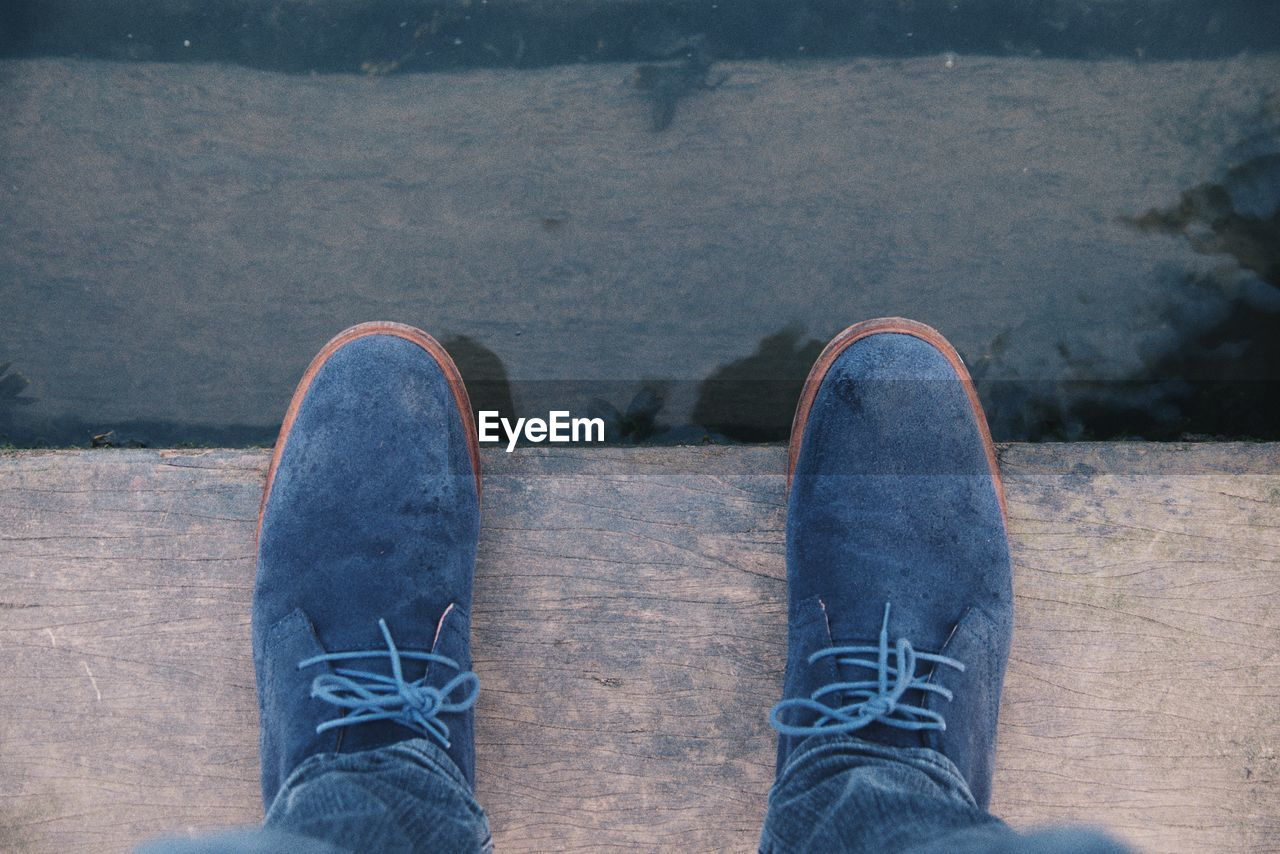Low section of person standing on wooden plank by the water