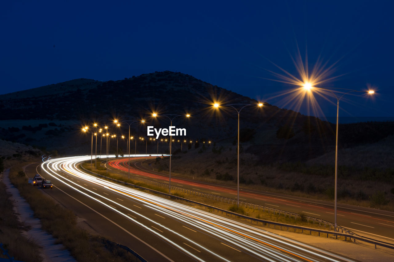 illuminated, night, light trail, speed, street light, long exposure, road, lighting equipment, transportation, motion, high street, outdoors, no people, clear sky, sky