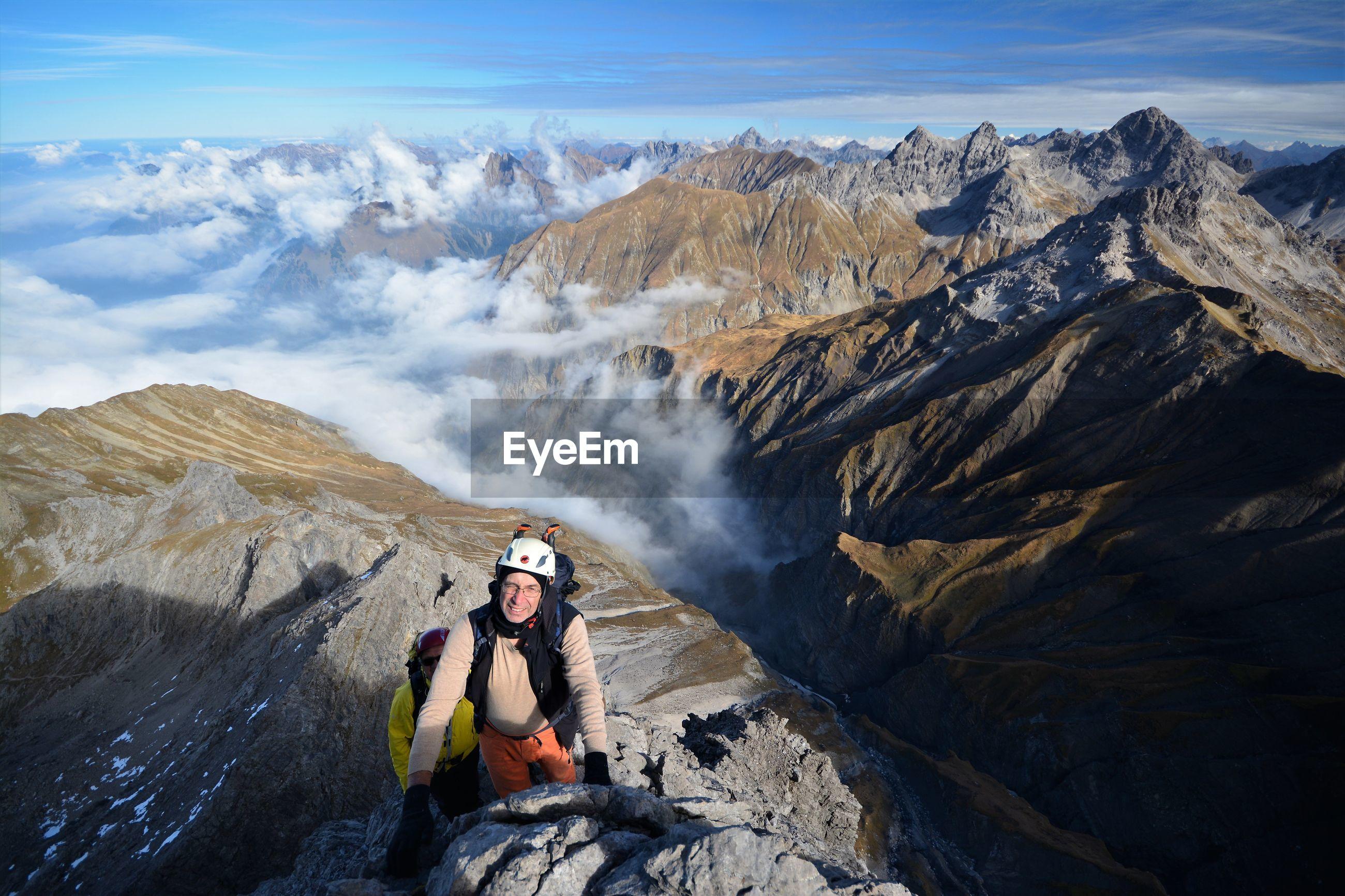 Portrait of senior man standing on mountain against sky