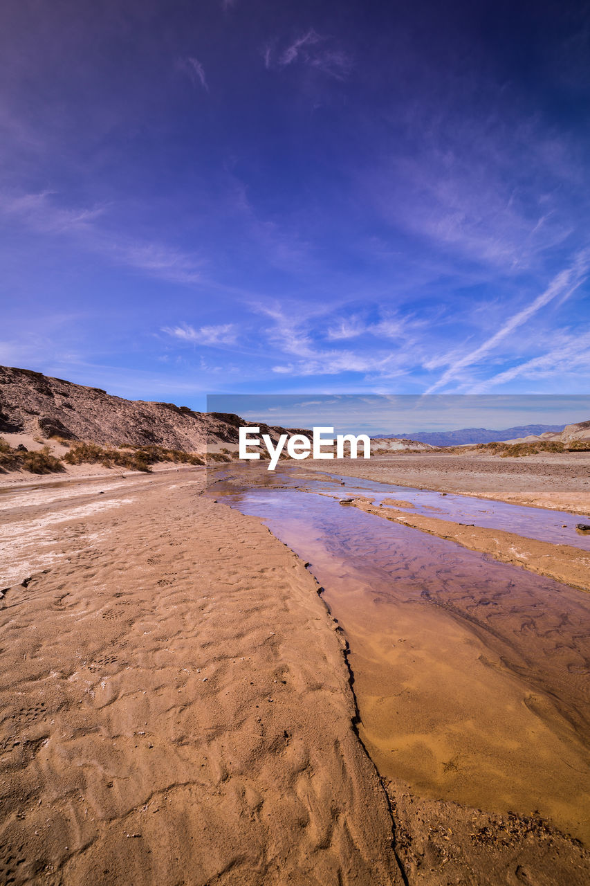sky, scenics - nature, beauty in nature, tranquil scene, tranquility, cloud - sky, non-urban scene, land, blue, environment, landscape, sand, nature, no people, water, idyllic, remote, desert, day, climate, arid climate, salt flat