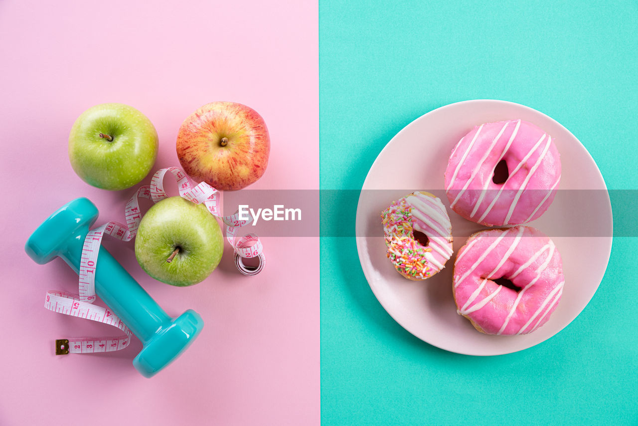 food, food and drink, fruit, still life, healthy eating, freshness, wellbeing, indoors, apple - fruit, studio shot, high angle view, no people, table, directly above, pink color, multi colored, sweet food, colored background, green color, indulgence, temptation