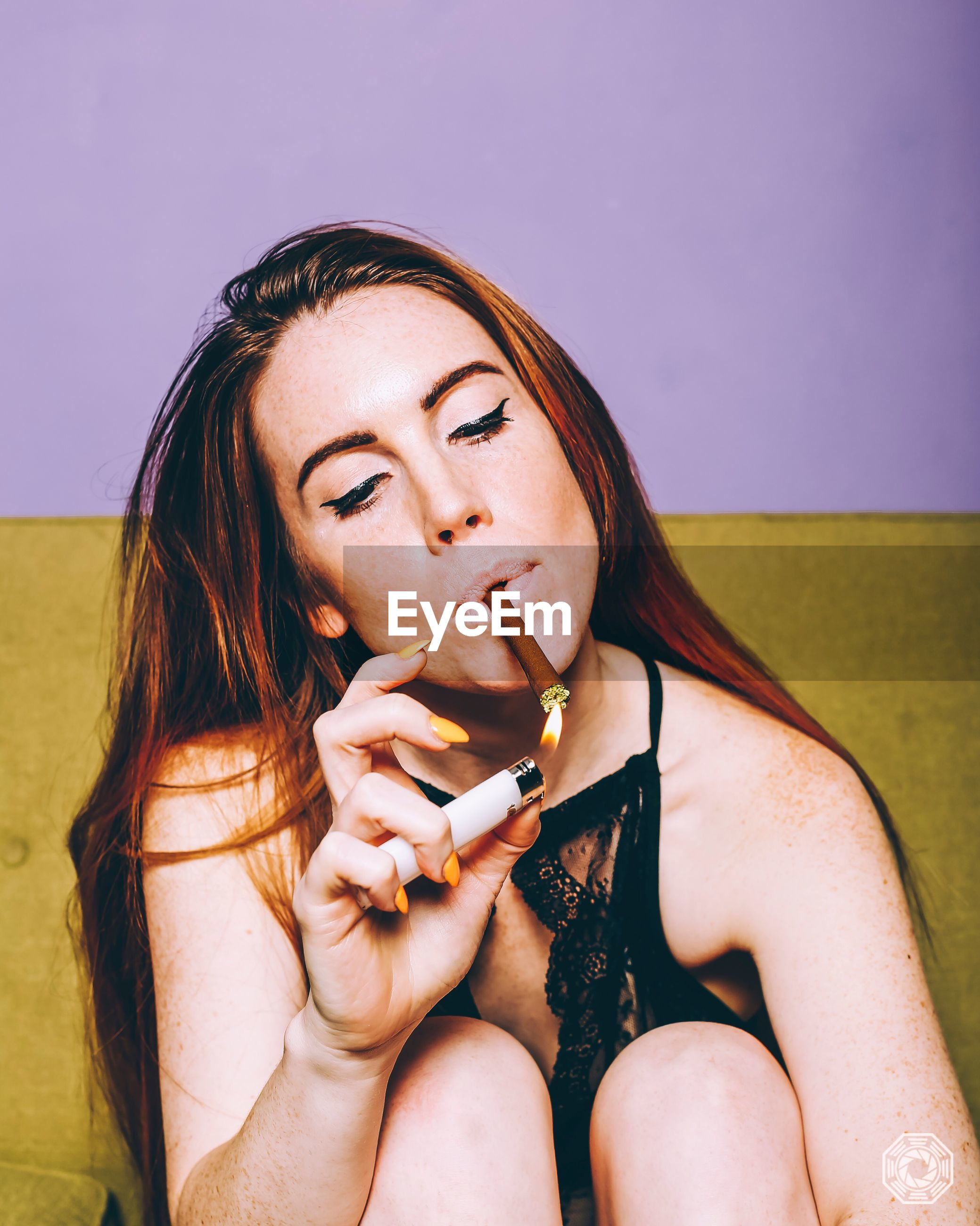 smoking issues, addiction, bad habit, cigarette, real people, holding, one person, danger, leisure activity, smoking - activity, social issues, front view, risk, lifestyles, young women, young adult, sitting, studio shot, cigar, outdoors, day, close-up, people