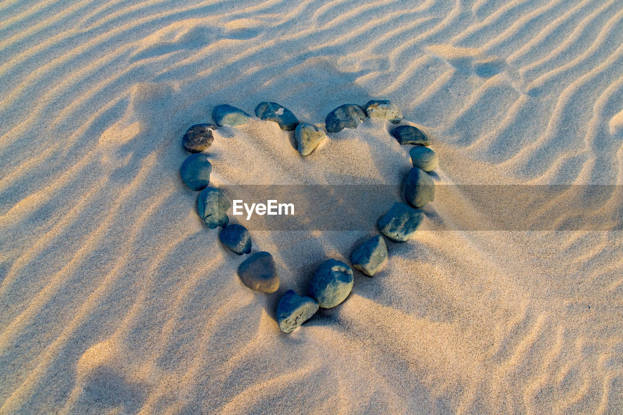 sand, land, beach, high angle view, no people, nature, love, positive emotion, heart shape, pattern, emotion, footprint, outdoors, day, representation, creativity, track - imprint, absence, close-up, landscape, pebble