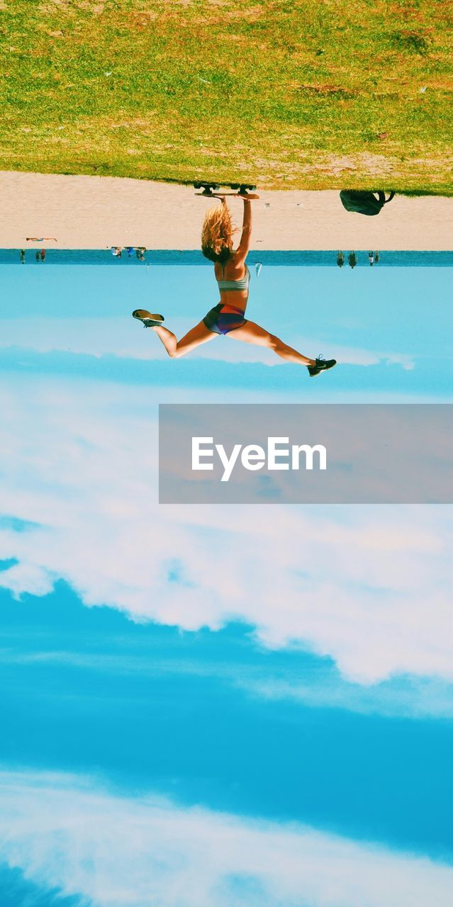 Upside Down Image Of Woman Doing Handstand On Skateboard Against Sky At Beach