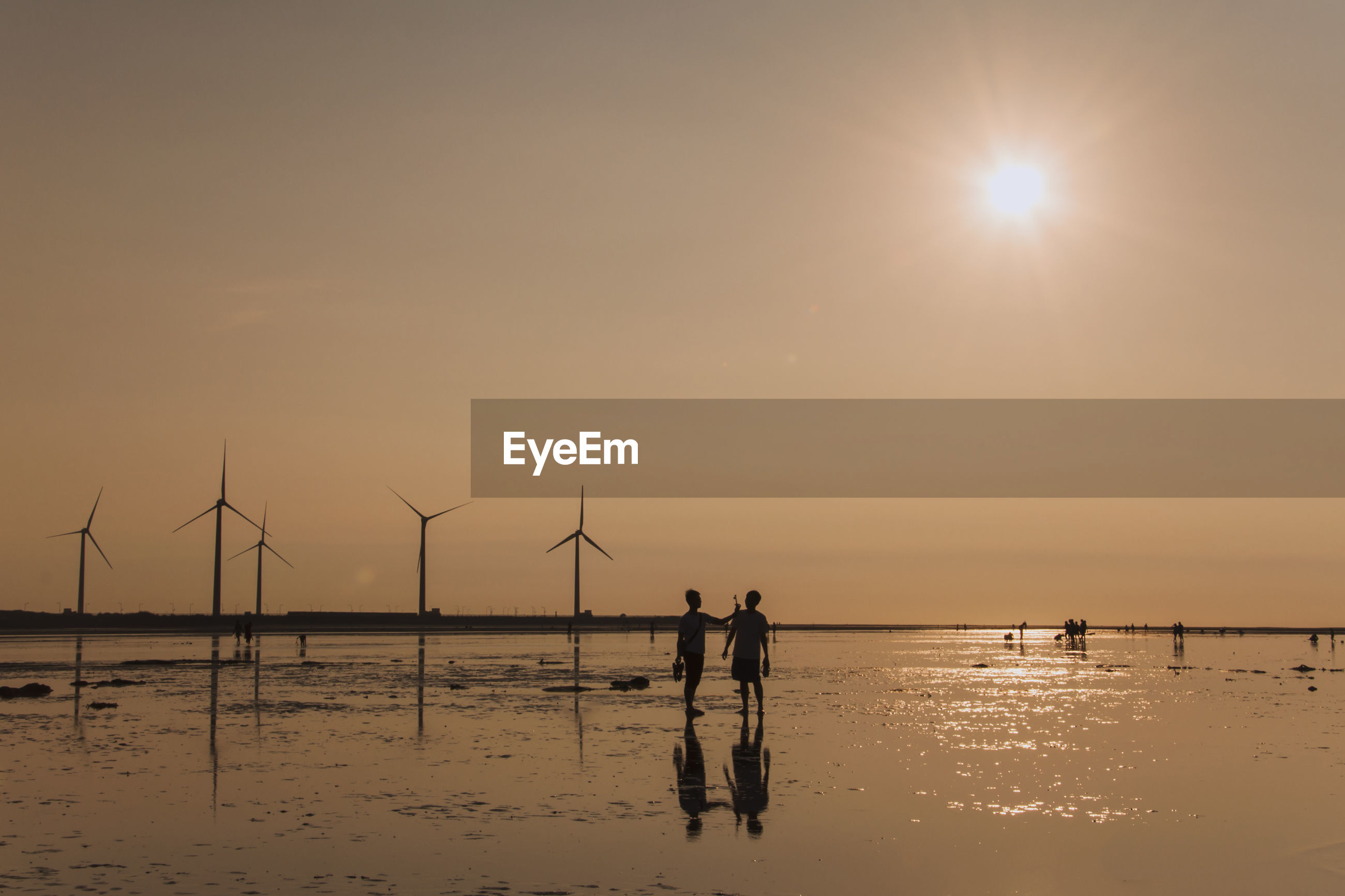 Silhouette people standing by windmills at wet beach during sunset