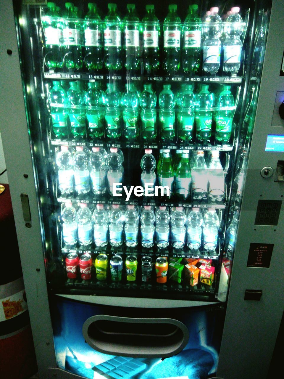 indoors, no people, illuminated, glass - material, close-up, in a row, container, machinery, technology, bottle, group, large group of objects, choice, glowing, control, multi colored, side by side, metal, business, food and drink, vending machine
