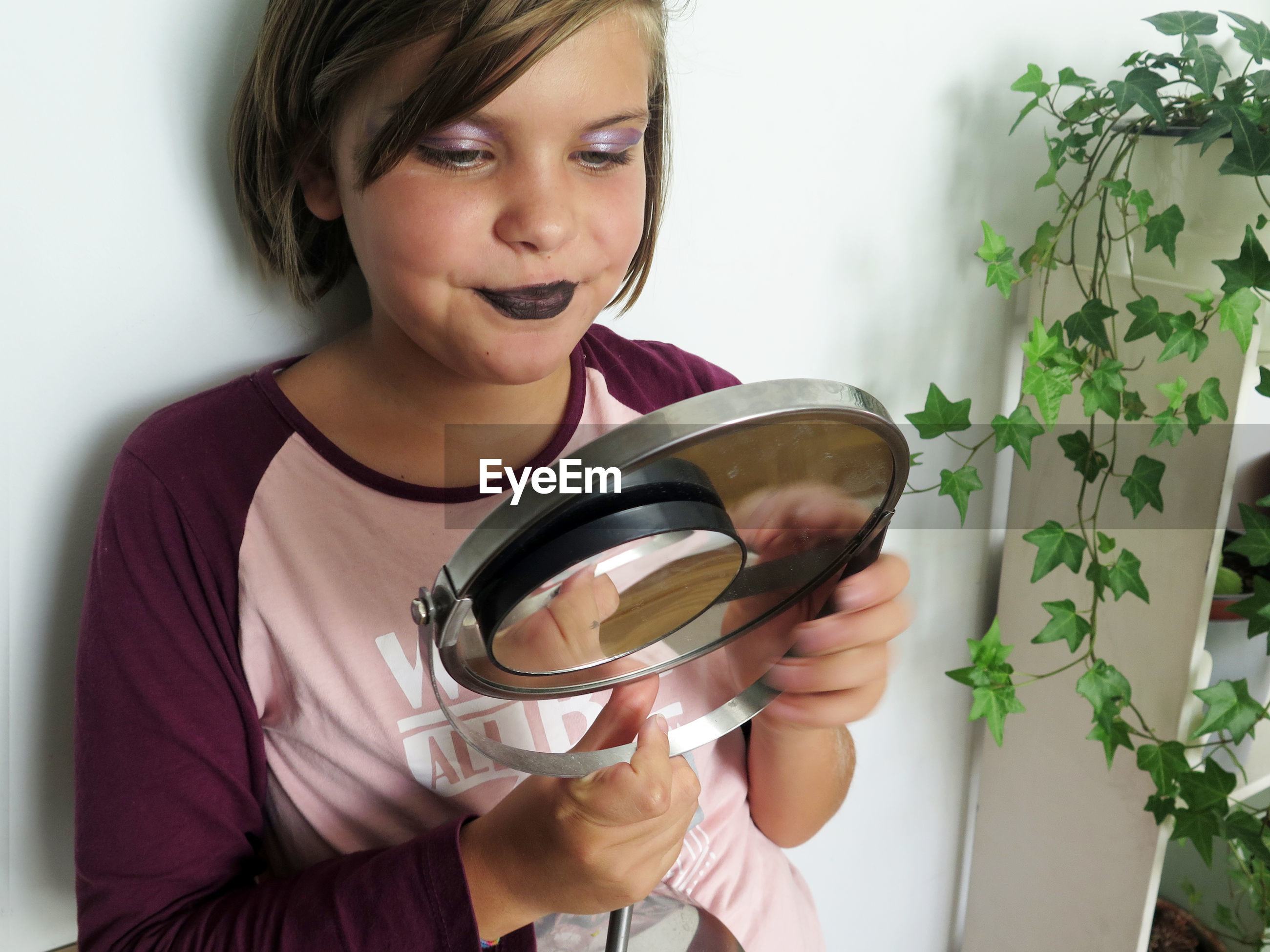 Girl with make-up looking into mirror at home