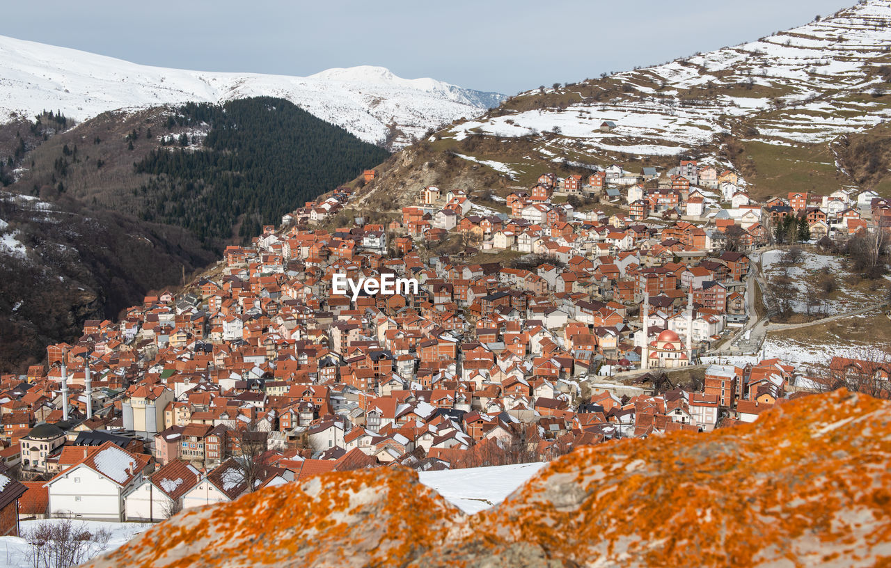 AERIAL VIEW OF TOWNSCAPE AND SNOWCAPPED MOUNTAIN
