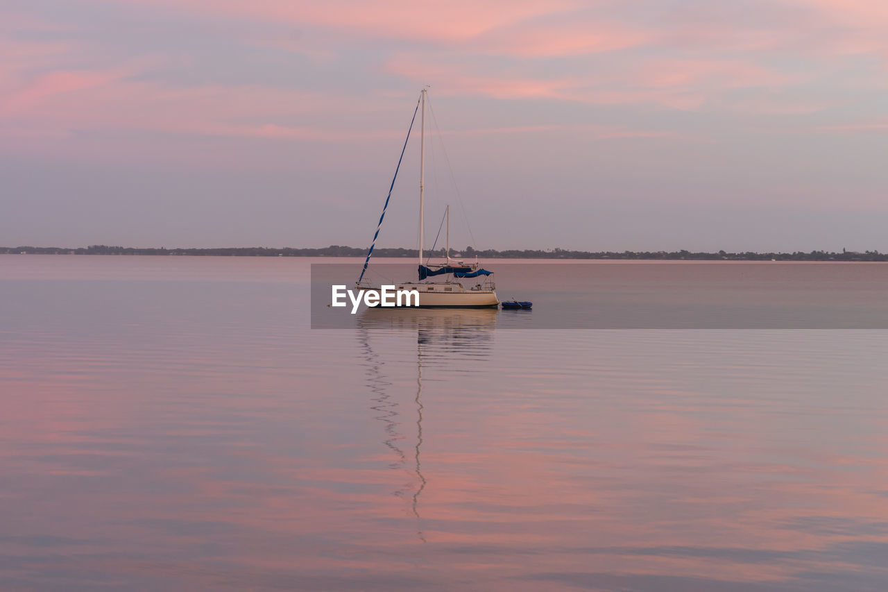 water, sunset, reflection, waterfront, nature, sky, nautical vessel, tranquility, beauty in nature, transportation, scenics, sea, cloud - sky, tranquil scene, outdoors, mode of transport, no people, sailboat, mast, sailing, day