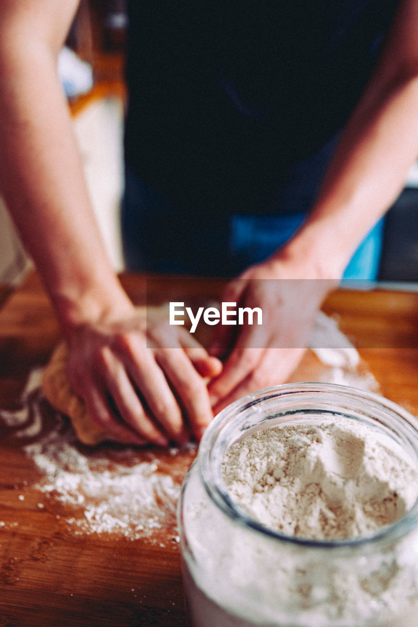 Midsection of person kneading dough in kitchen
