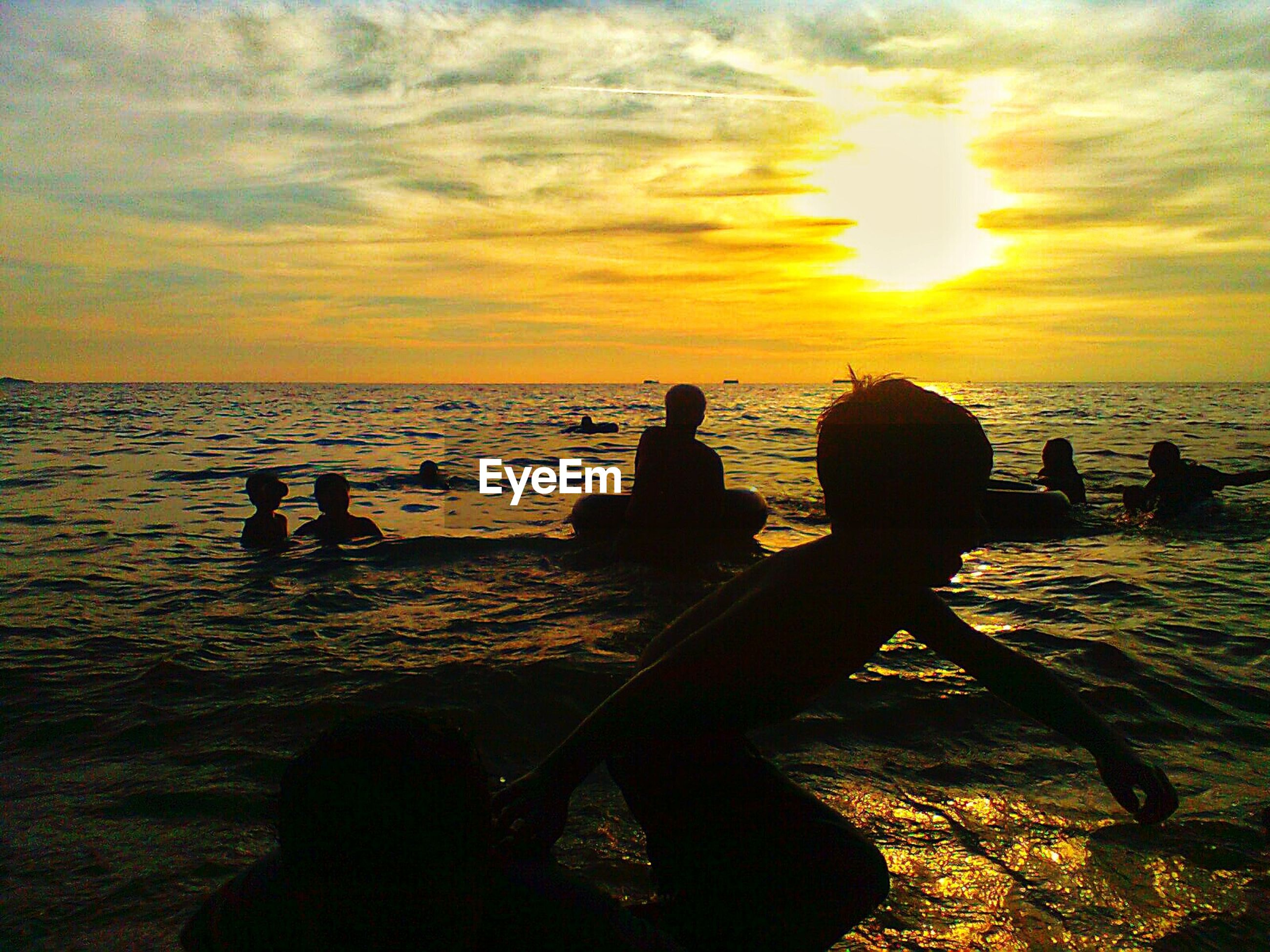 Children playing in sea during sunset