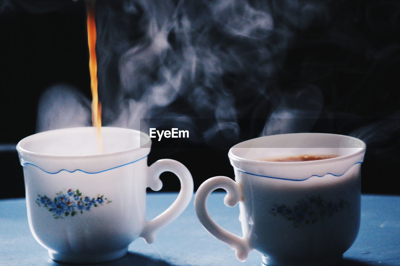 Close-Up Of Tea Being Poured In Cup On Table