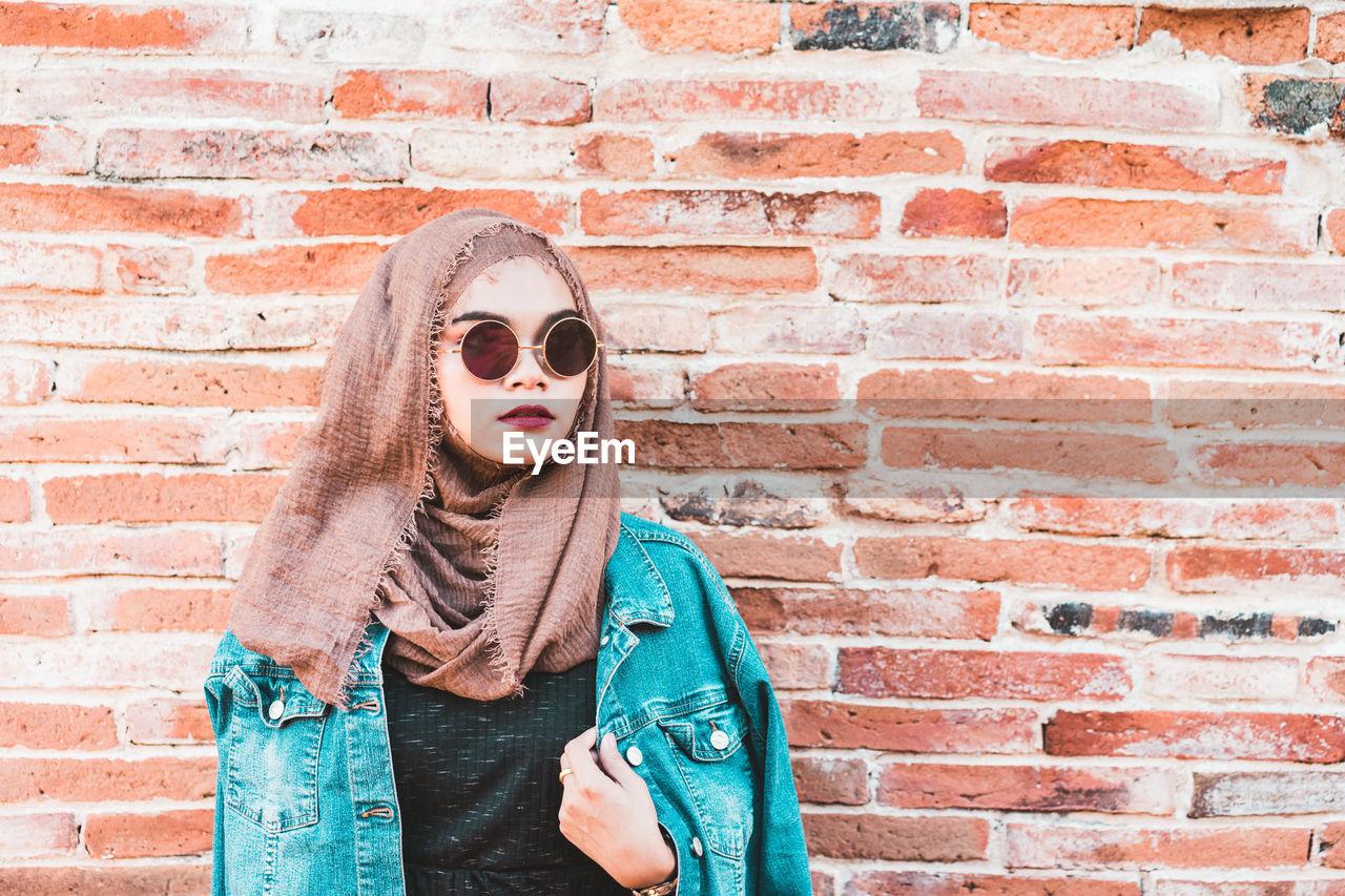 Portrait of woman wearing sunglasses against brick wall