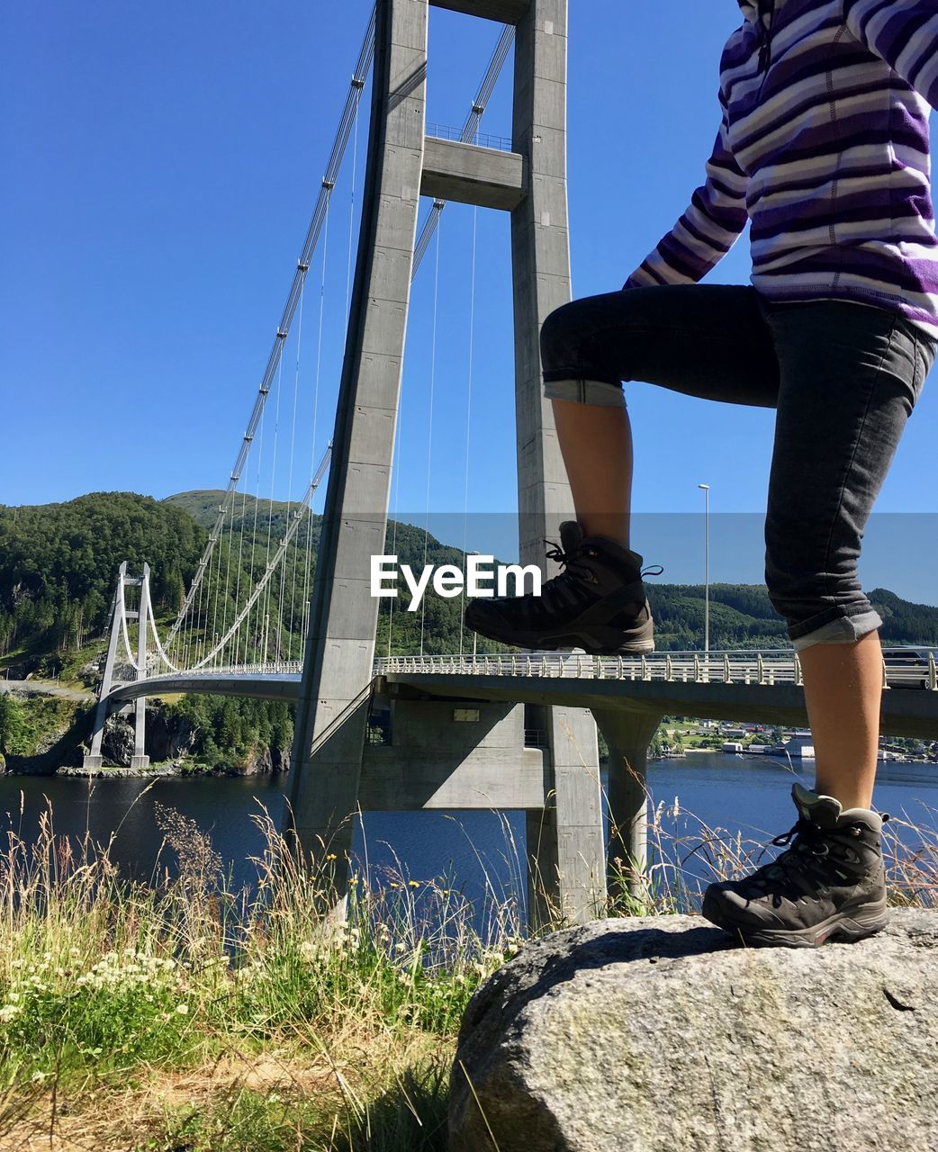 low section, real people, lifestyles, one person, leisure activity, day, outdoors, clear sky, shoe, casual clothing, sky, human leg, blue, nature, standing, climbing, water