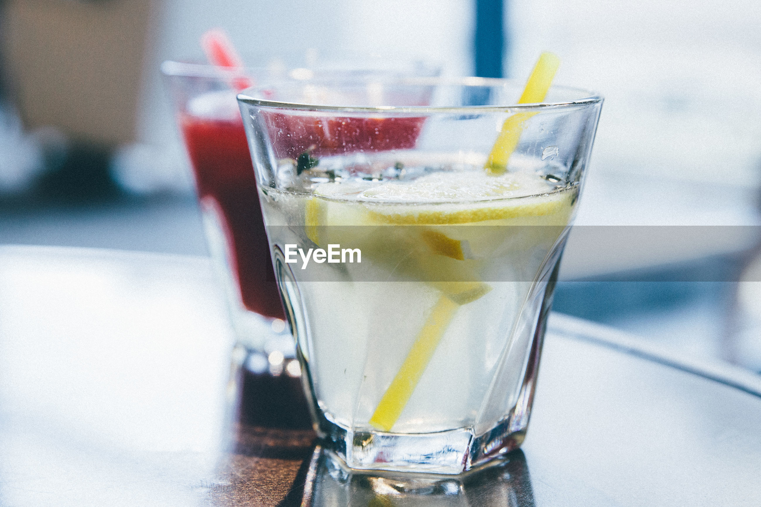 Close-up of lemonade with drink on table