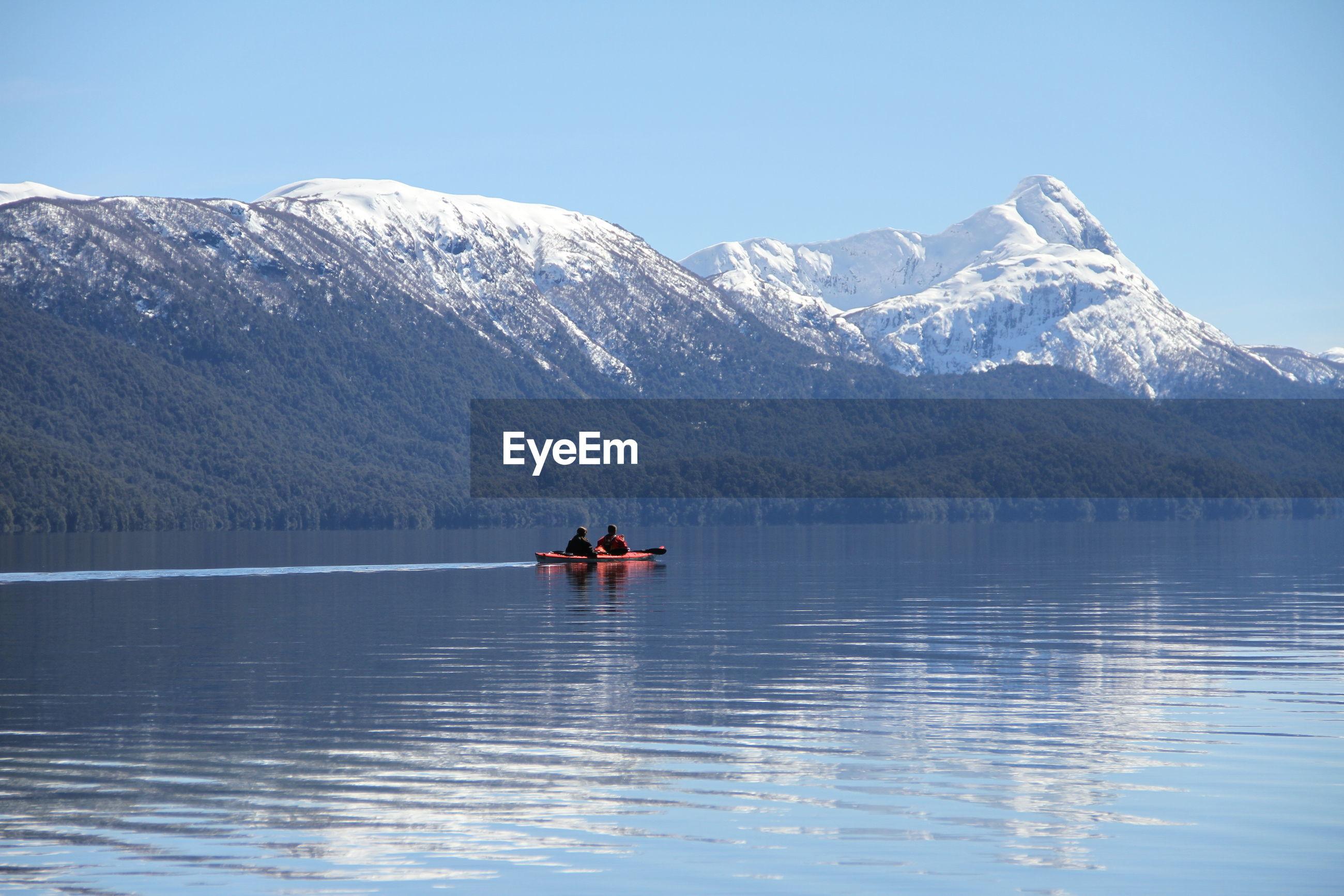 People kayaking on lake against mountains