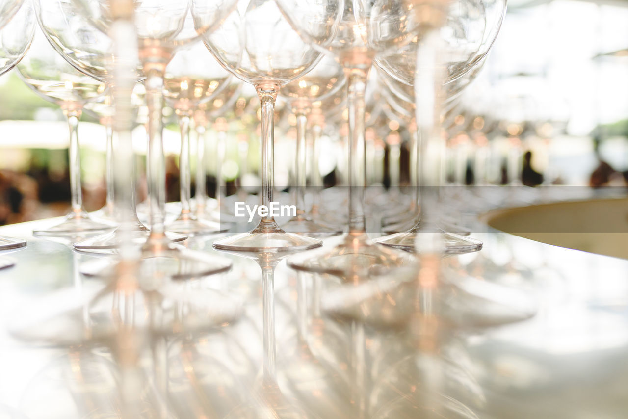 selective focus, glass, table, wineglass, glass - material, transparent, indoors, food and drink, no people, still life, refreshment, drinking glass, household equipment, drink, reflection, close-up, large group of objects, day, restaurant, alcohol, surface level, setting, luxury