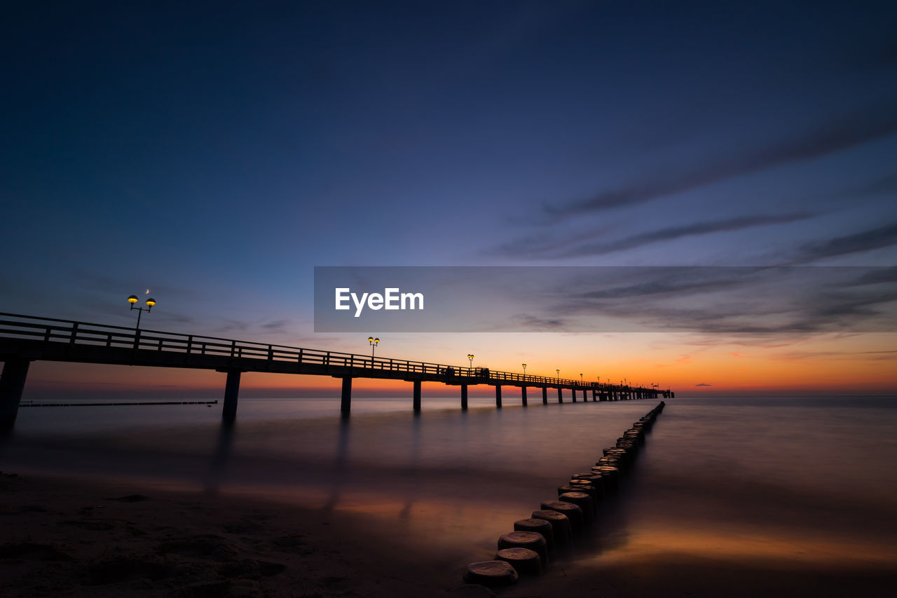 sky, sunset, water, beauty in nature, scenics - nature, cloud - sky, bridge, connection, nature, built structure, tranquil scene, sea, tranquility, bridge - man made structure, architecture, orange color, no people, idyllic, pier, outdoors, horizon over water