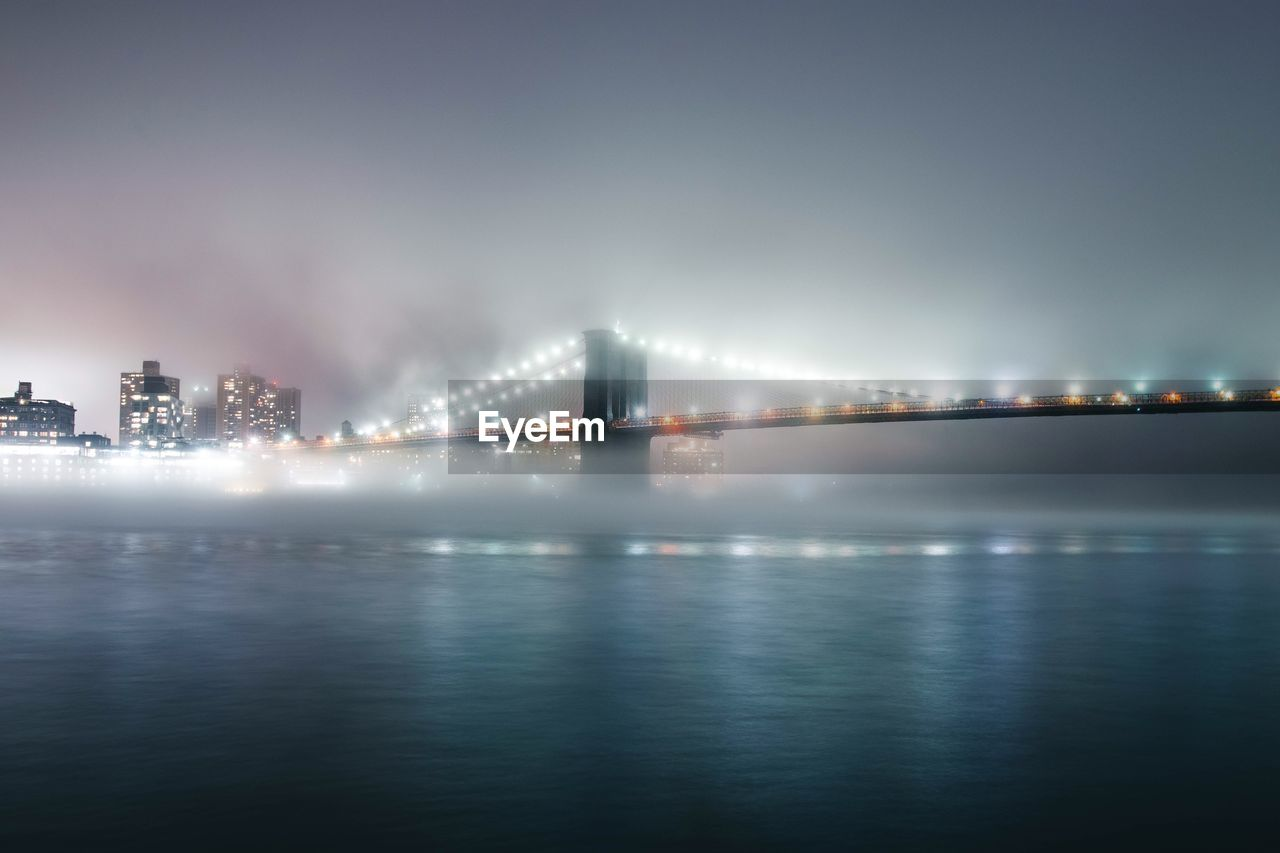 Illuminated Brooklyn Bridge Over River At Night