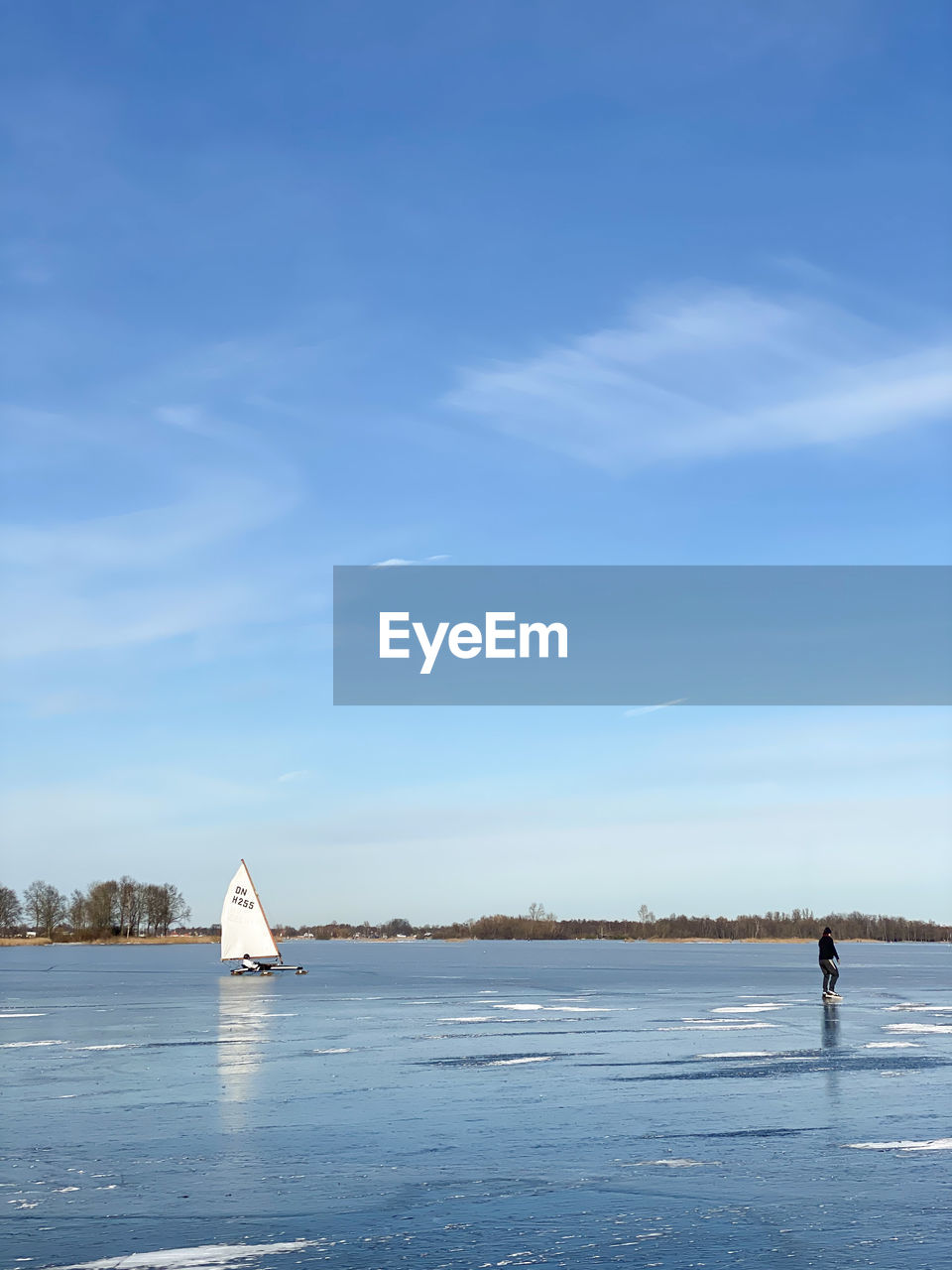 VIEW OF FROZEN LAKE AGAINST BLUE SKY