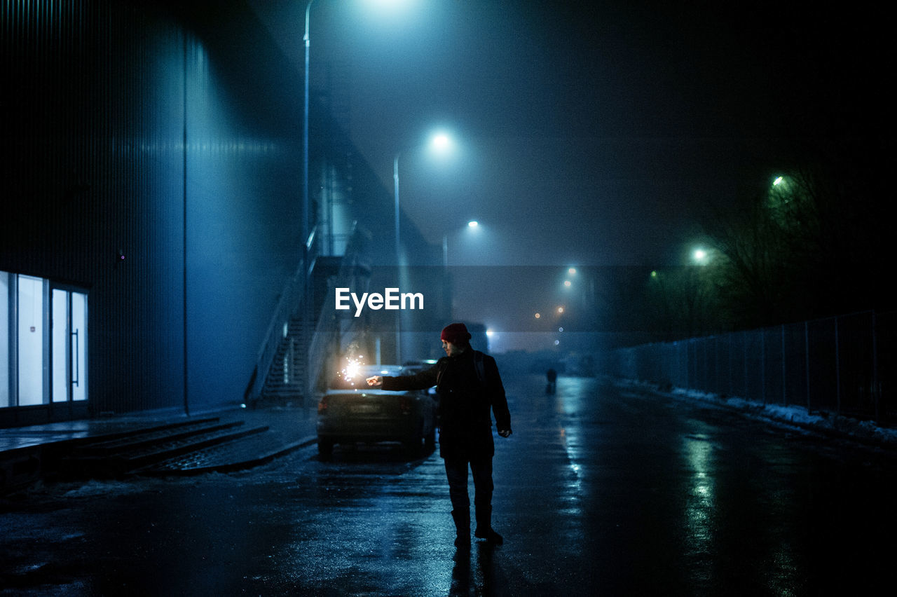 FULL LENGTH OF MAN STANDING ON ILLUMINATED STREET AT NIGHT