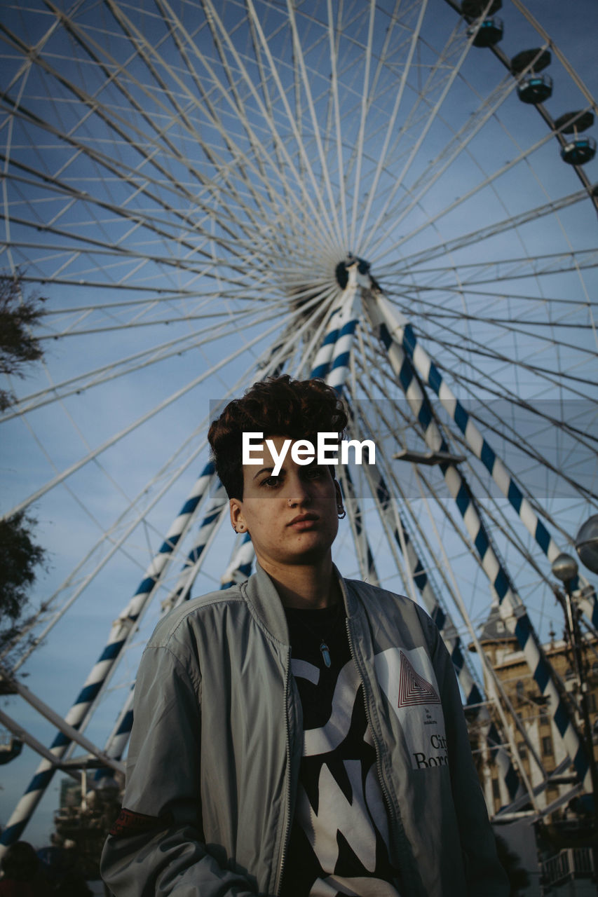 young men, portrait, leisure activity, young adult, one person, front view, looking at camera, real people, ferris wheel, casual clothing, amusement park, amusement park ride, lifestyles, waist up, day, sky, arts culture and entertainment, outdoors, teenager, contemplation