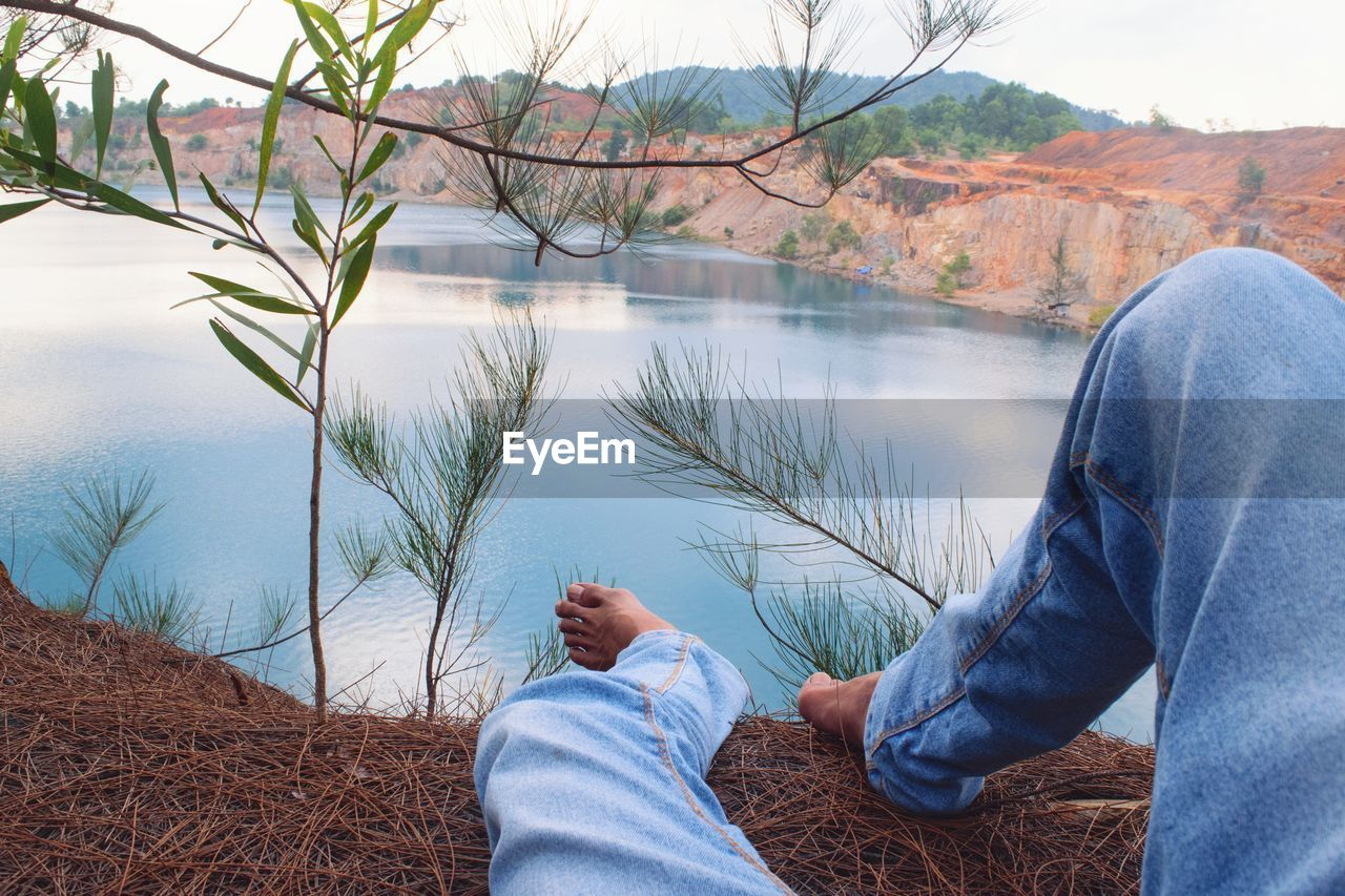 water, real people, low section, lifestyles, human leg, one person, human body part, body part, plant, lake, casual clothing, nature, leisure activity, day, men, relaxation, tree, personal perspective, outdoors, jeans, human foot, couple - relationship