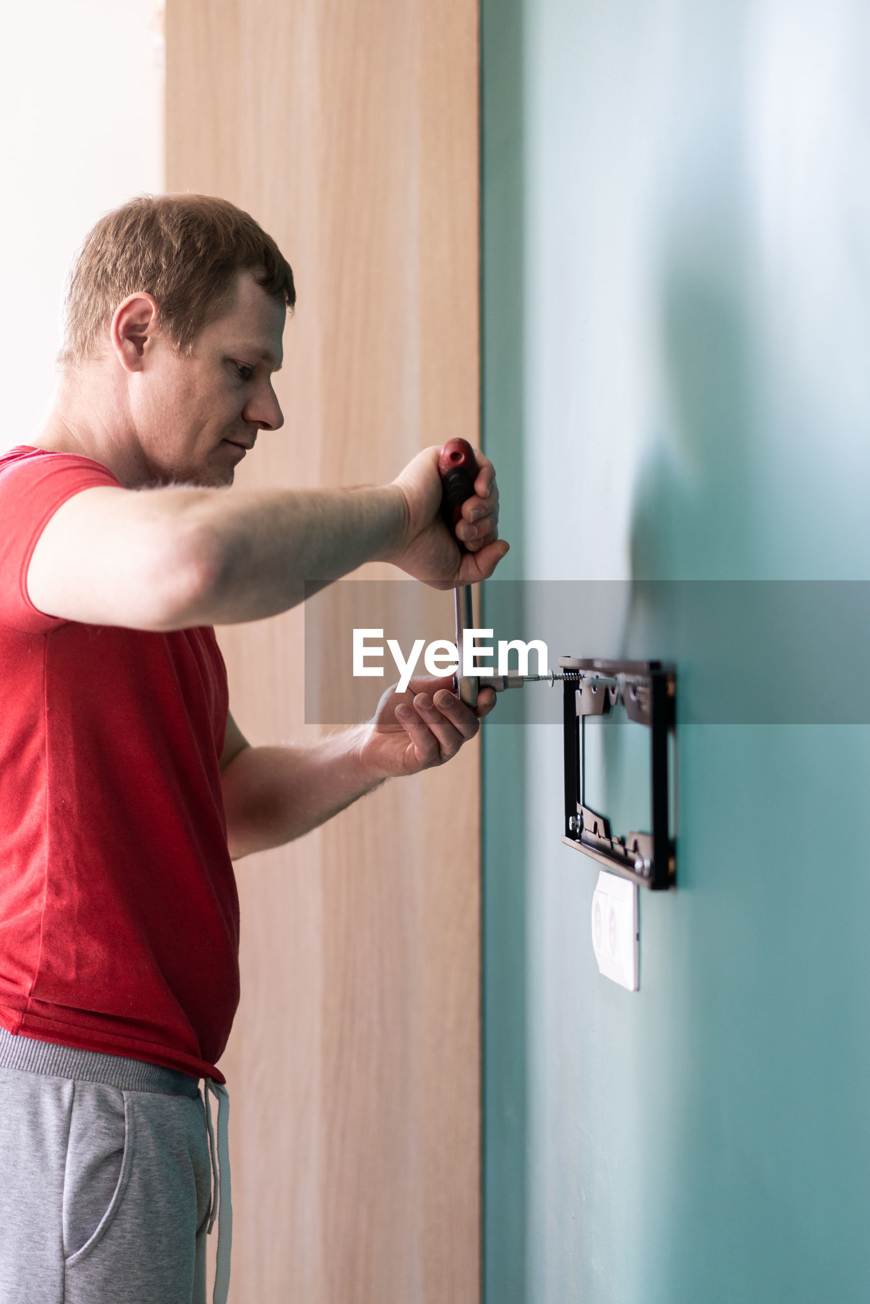 Side view of man installing equipment on wall at home