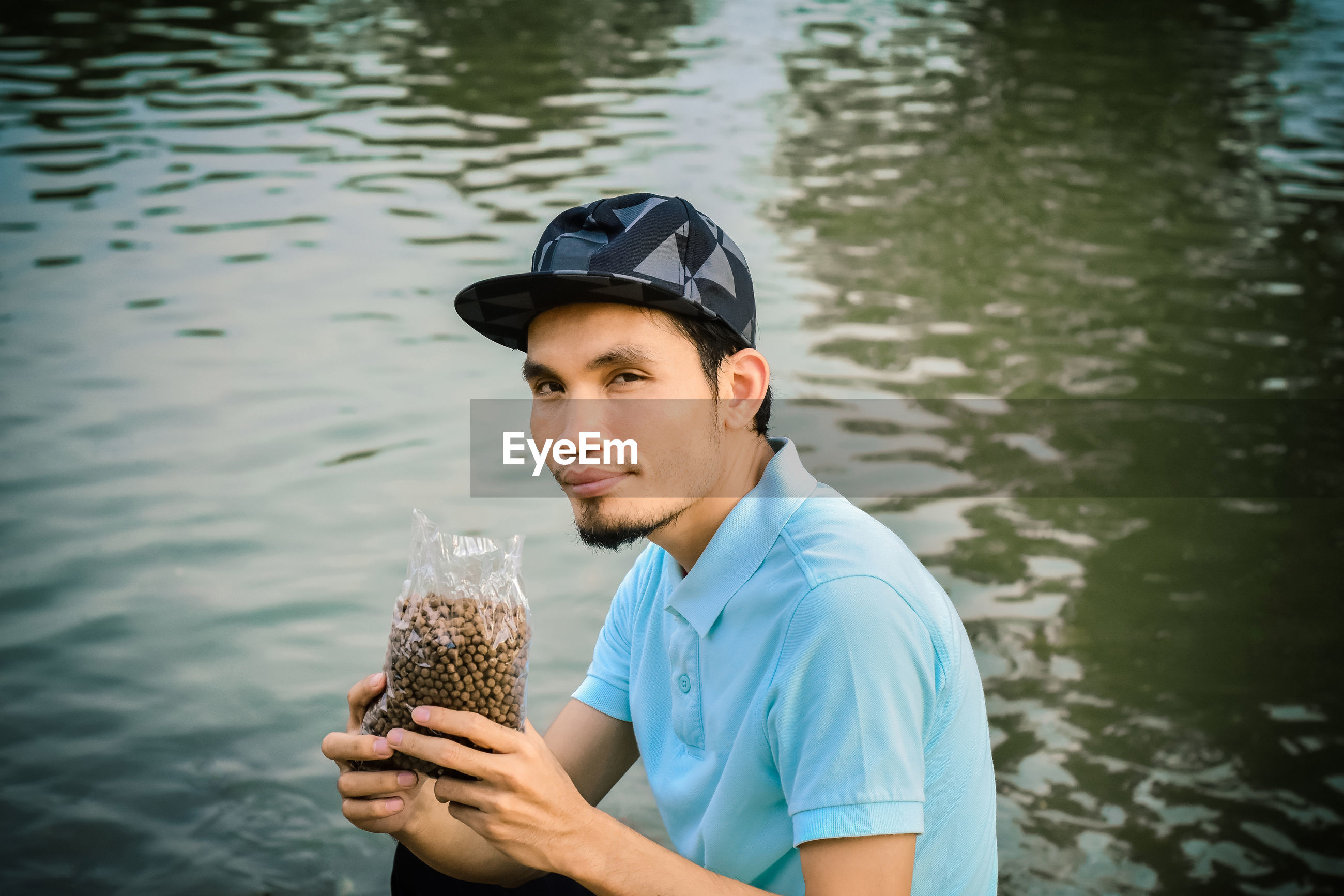 Portrait of man holding seeds in package while sitting against lake