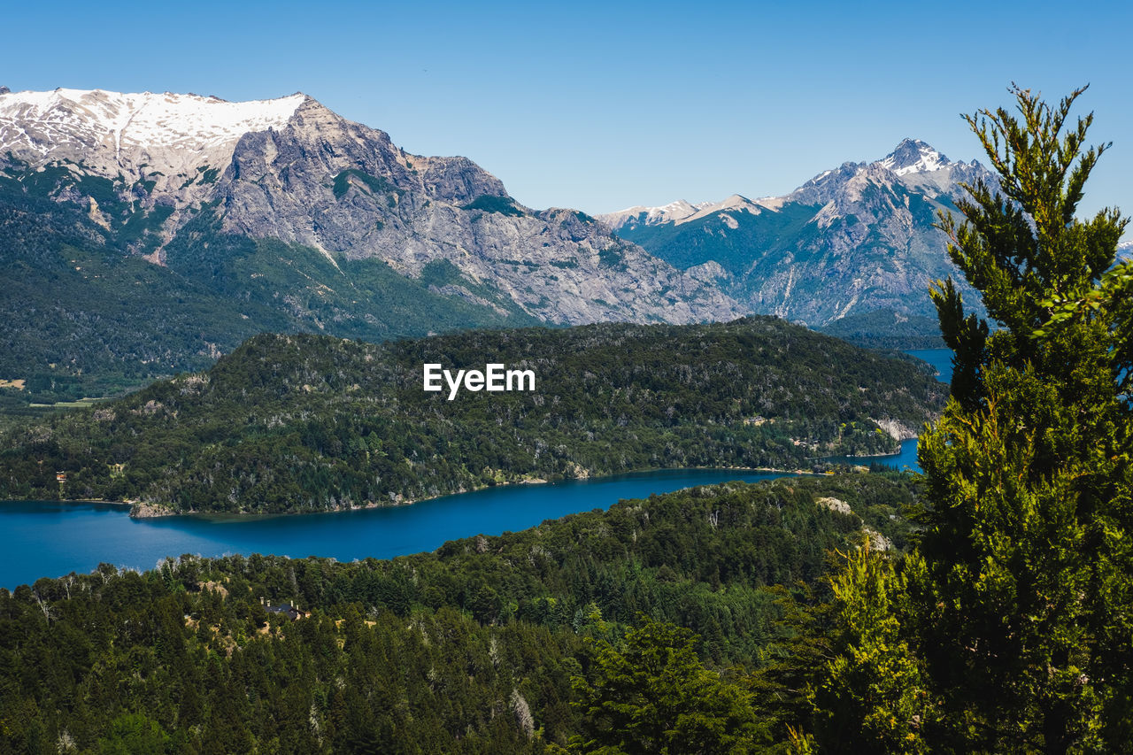 mountain, scenics - nature, beauty in nature, mountain range, tranquil scene, sky, water, tranquility, tree, plant, lake, non-urban scene, no people, nature, idyllic, day, landscape, clear sky, green color, mountain peak, snowcapped mountain, formation