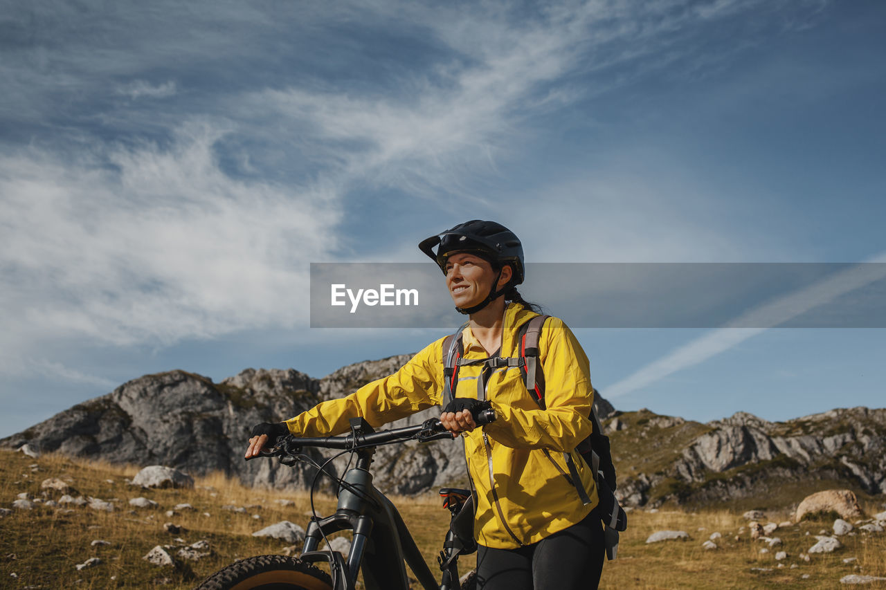 MAN STANDING BY BICYCLE AGAINST SKY