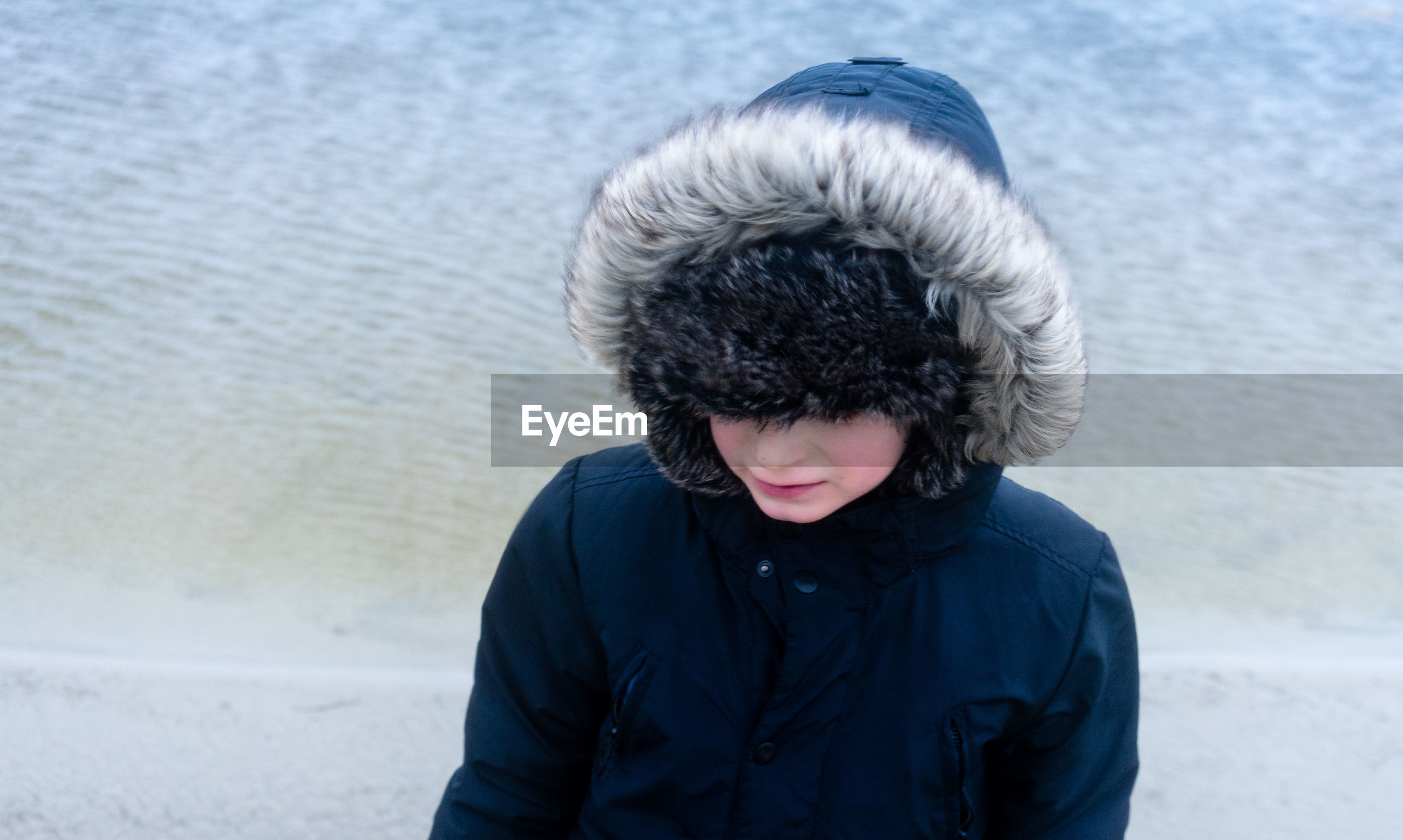 High angle view of woman wearing fur coat at beach during winter