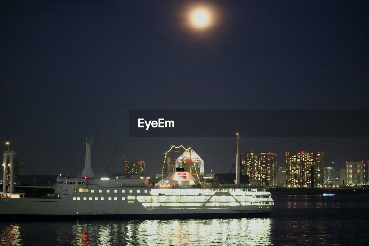 night, illuminated, building exterior, built structure, architecture, waterfront, water, nautical vessel, river, no people, sky, city, moon, travel destinations, skyscraper, outdoors, harbor, clear sky, cityscape, nature