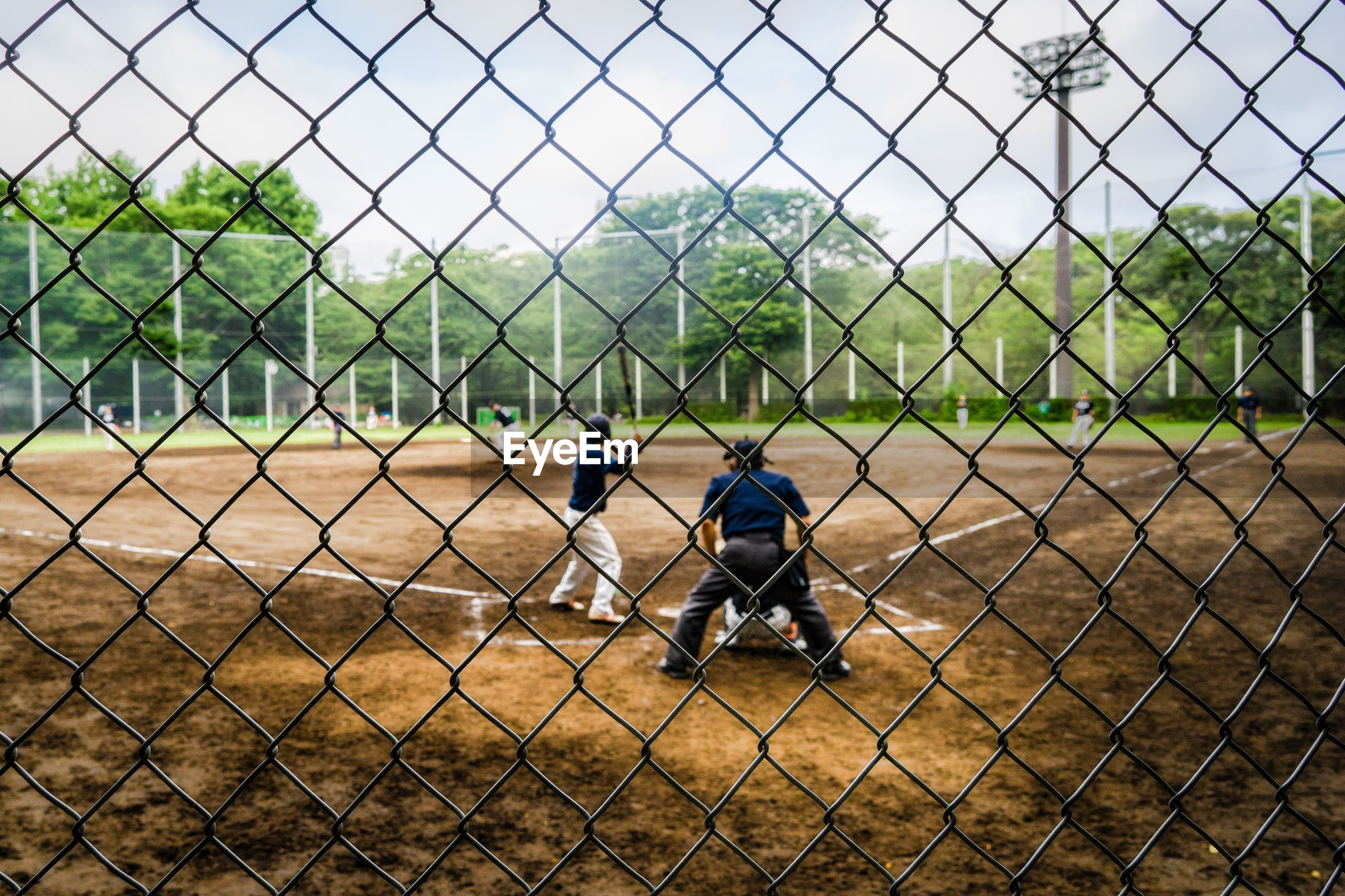 People playing seen through chainlink fence