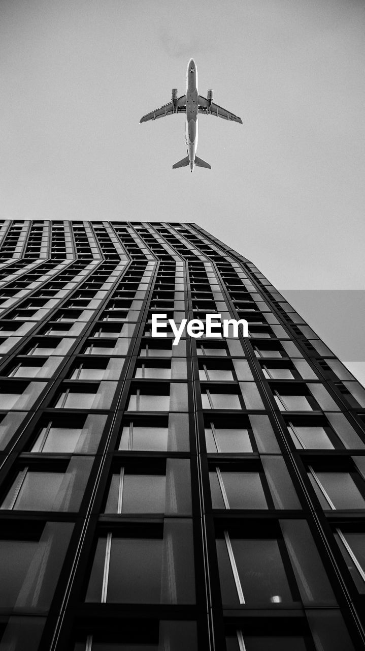 low angle view, building exterior, architecture, built structure, air vehicle, sky, building, flying, airplane, city, no people, office building exterior, tall - high, day, transportation, mode of transportation, skyscraper, clear sky, nature, travel, outdoors, modern, directly below
