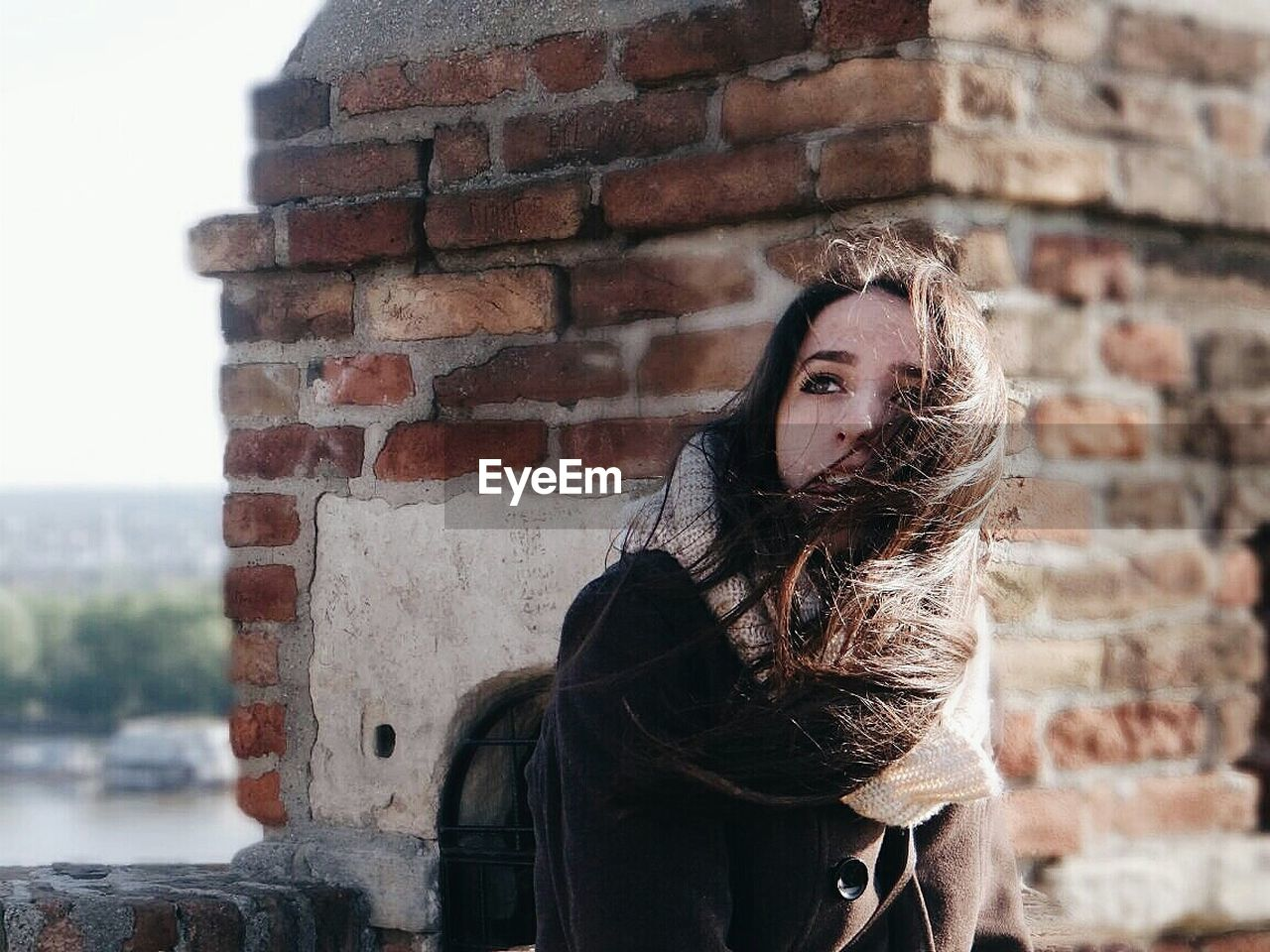 brick wall, one person, young adult, young women, beautiful woman, real people, outdoors, lifestyles, leisure activity, long hair, architecture, built structure, looking at camera, day, building exterior, portrait, standing, warm clothing, adult, people