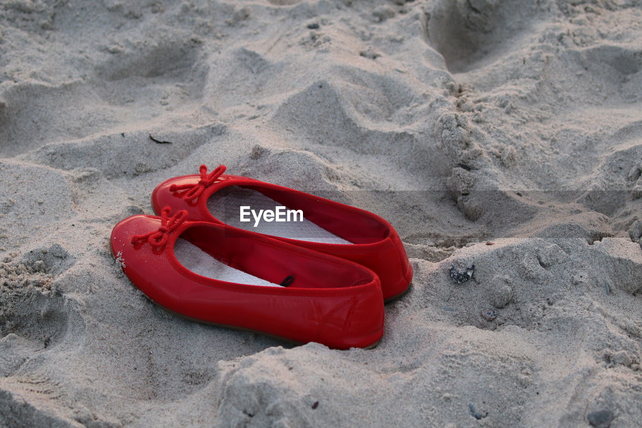 HIGH ANGLE VIEW OF RED ROSE ON SAND
